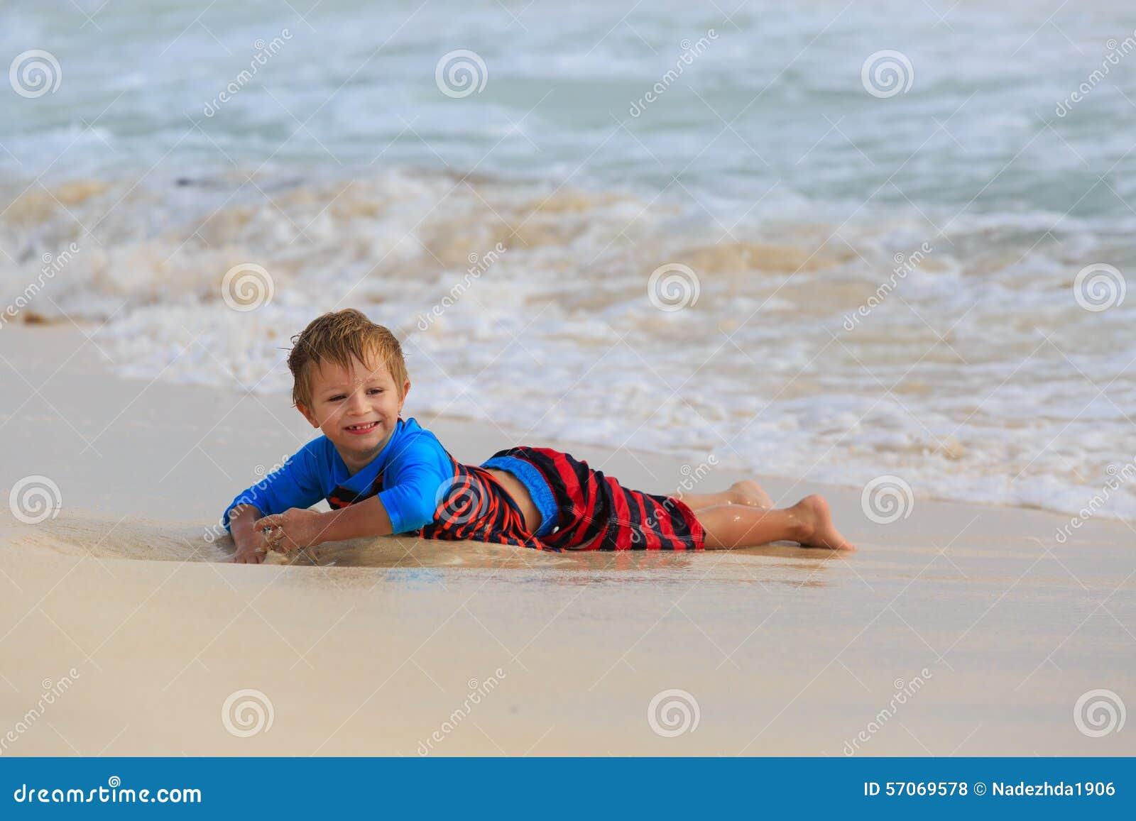 Weinig jongen die met golven op zandstrand spelen