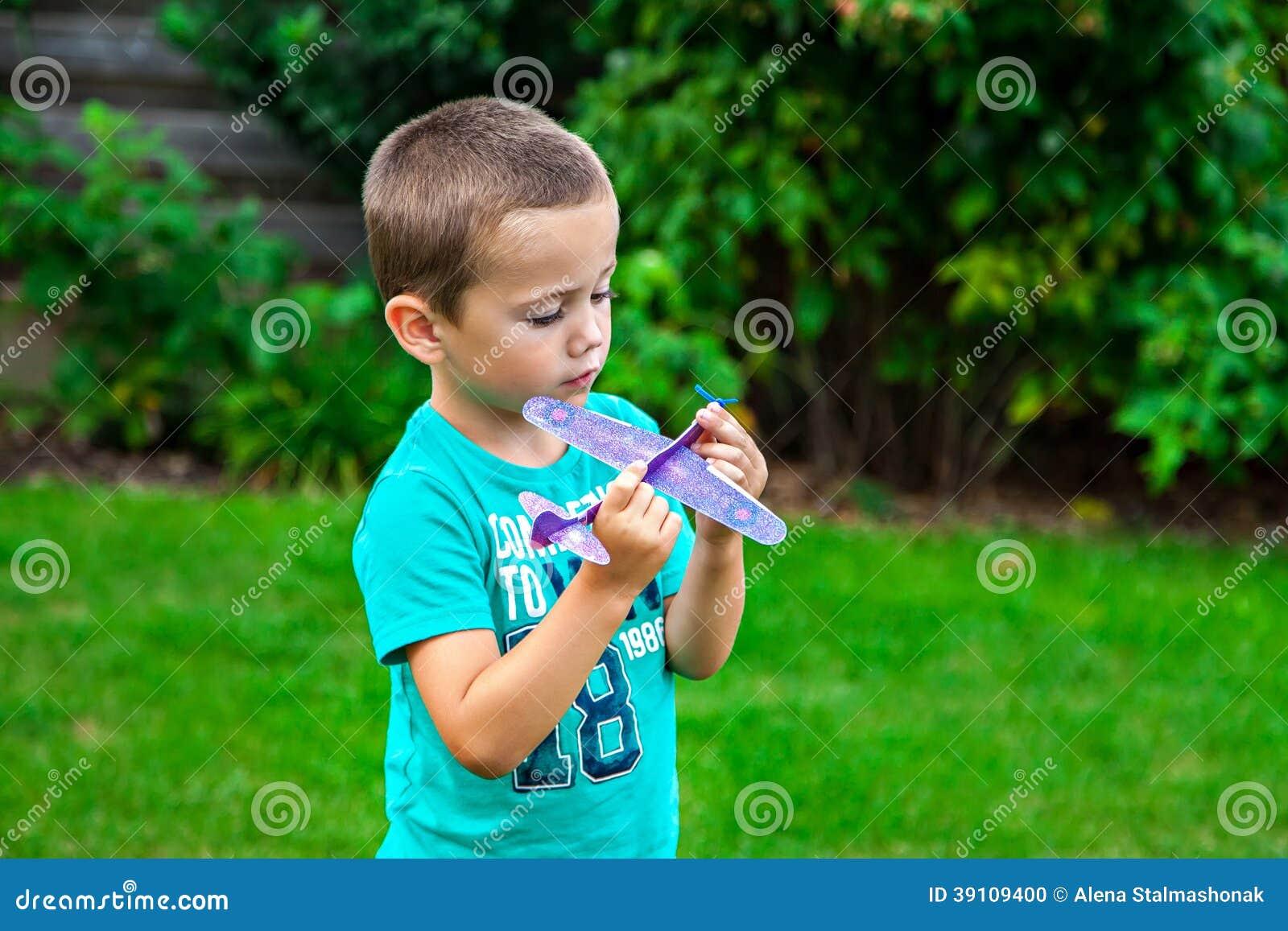Weinig jongen die met stuk speelgoed vliegtuig spelen