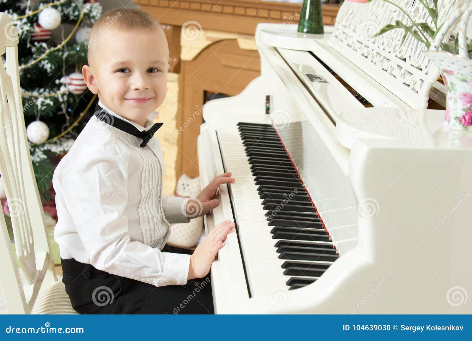 Download Weinig Jongen Die Op Een Witte Grote Piano Spelen Stock Foto - Afbeelding bestaande uit moeder, meisje: 104639030
