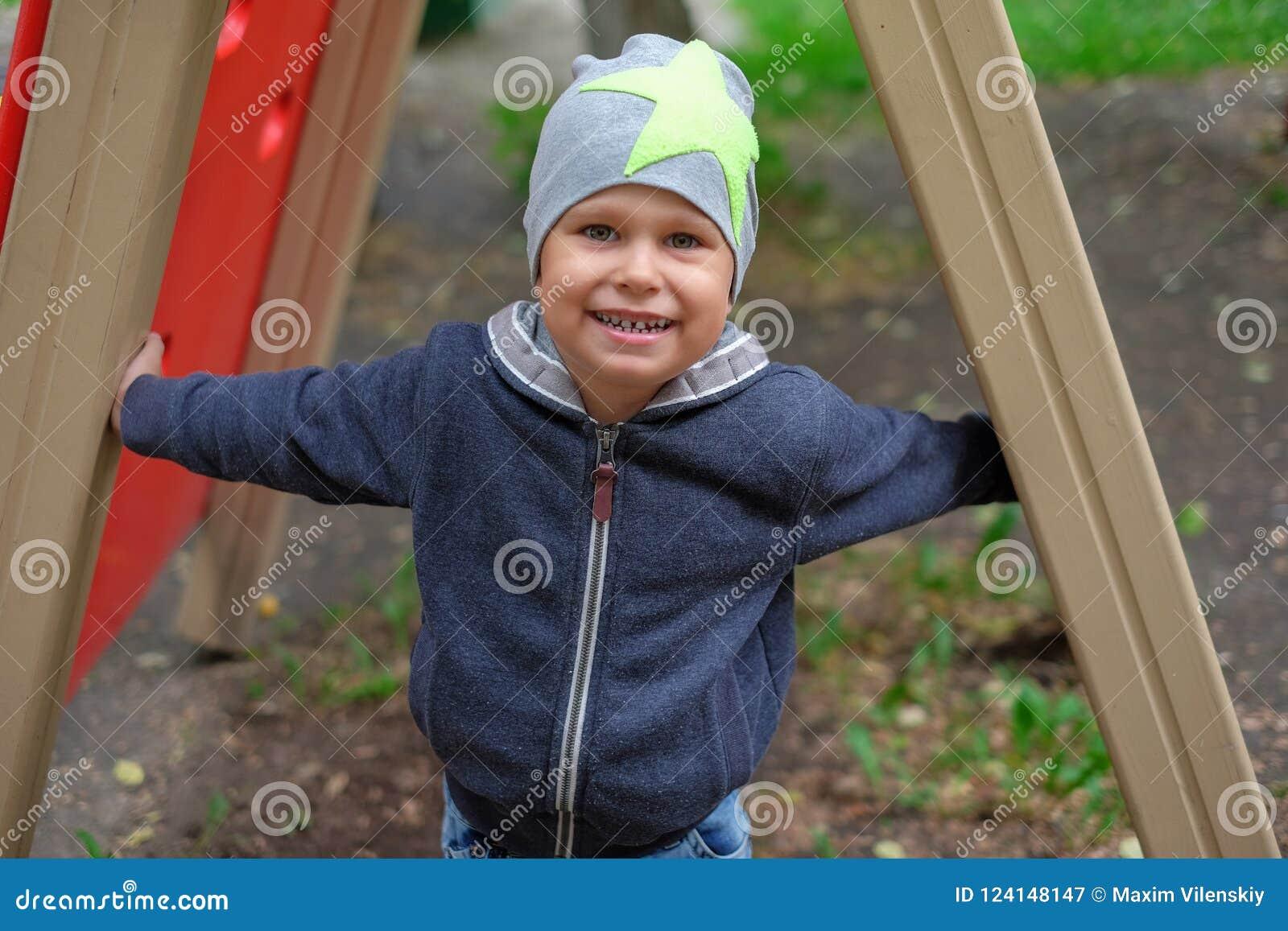 Weinig jongen die op speelplaats in openlucht de herfstpark spelen