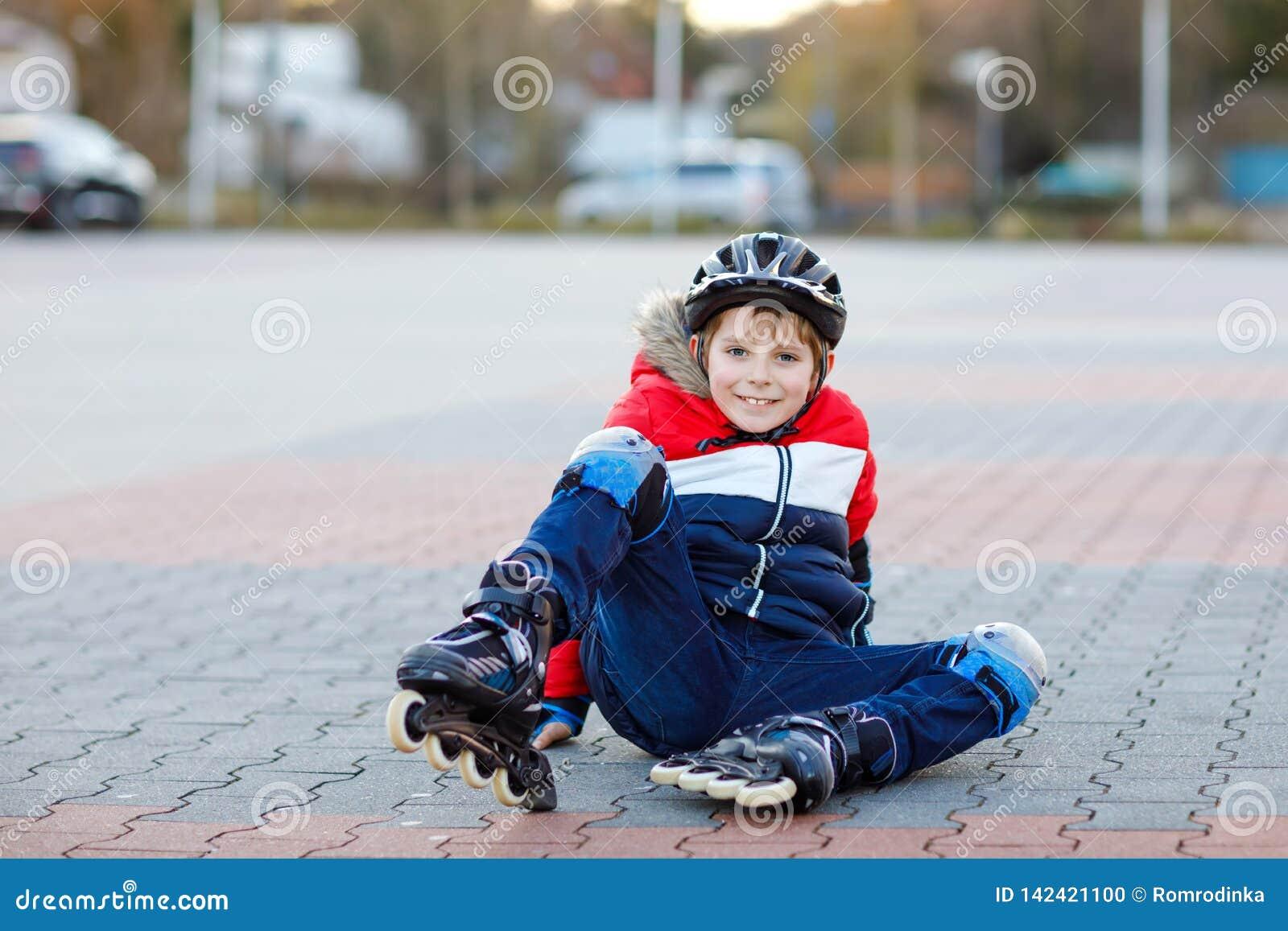 Weinig jongen die van het schooljonge geitje met rollen in de stad schaatsen kind in de kleren van de beschermingsveiligheid Het