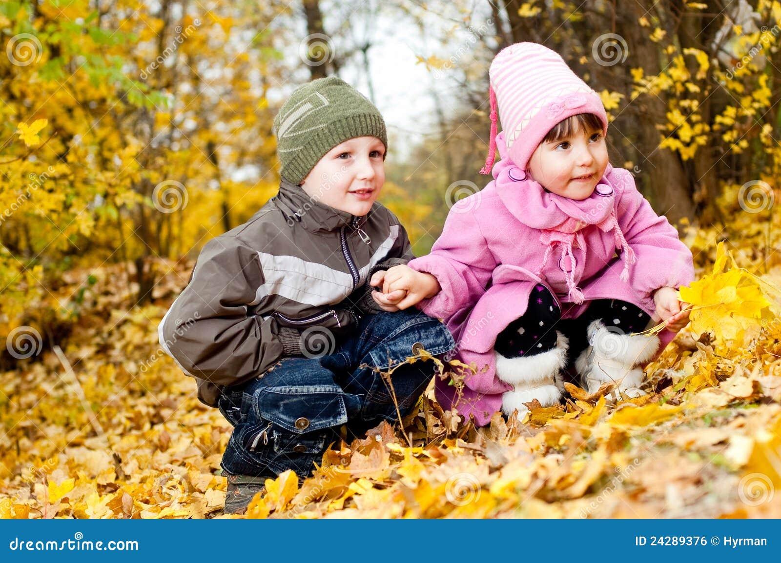 Weinig jongen en meisje spelen in een park in de herfst stock foto afbeelding 24289376 - Twee meisjes en een jongen ...
