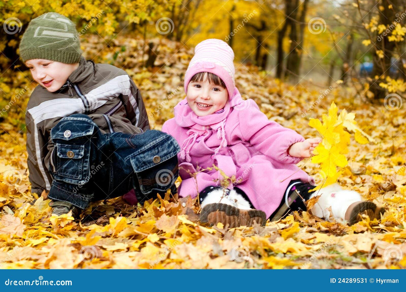 Weinig jongen en meisje spelen in een park in de herfst stock afbeelding afbeelding 24289531 - Twee meisjes en een jongen ...