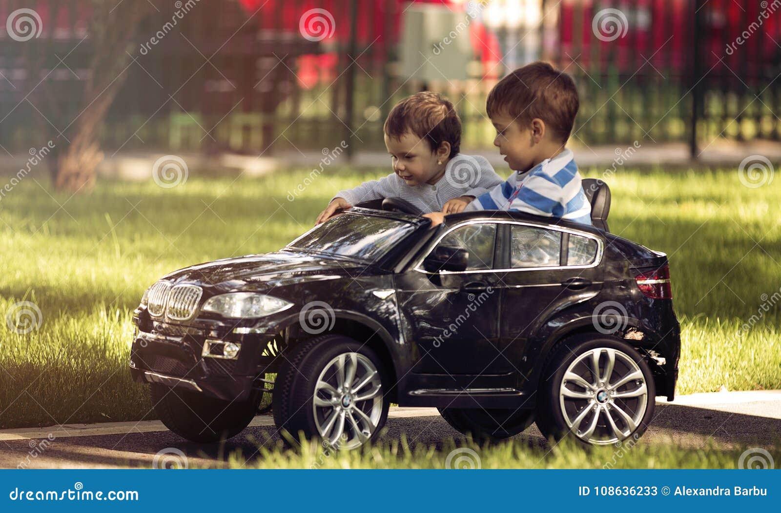 Weinig jongen en meisjes drijfstuk speelgoed auto in een park