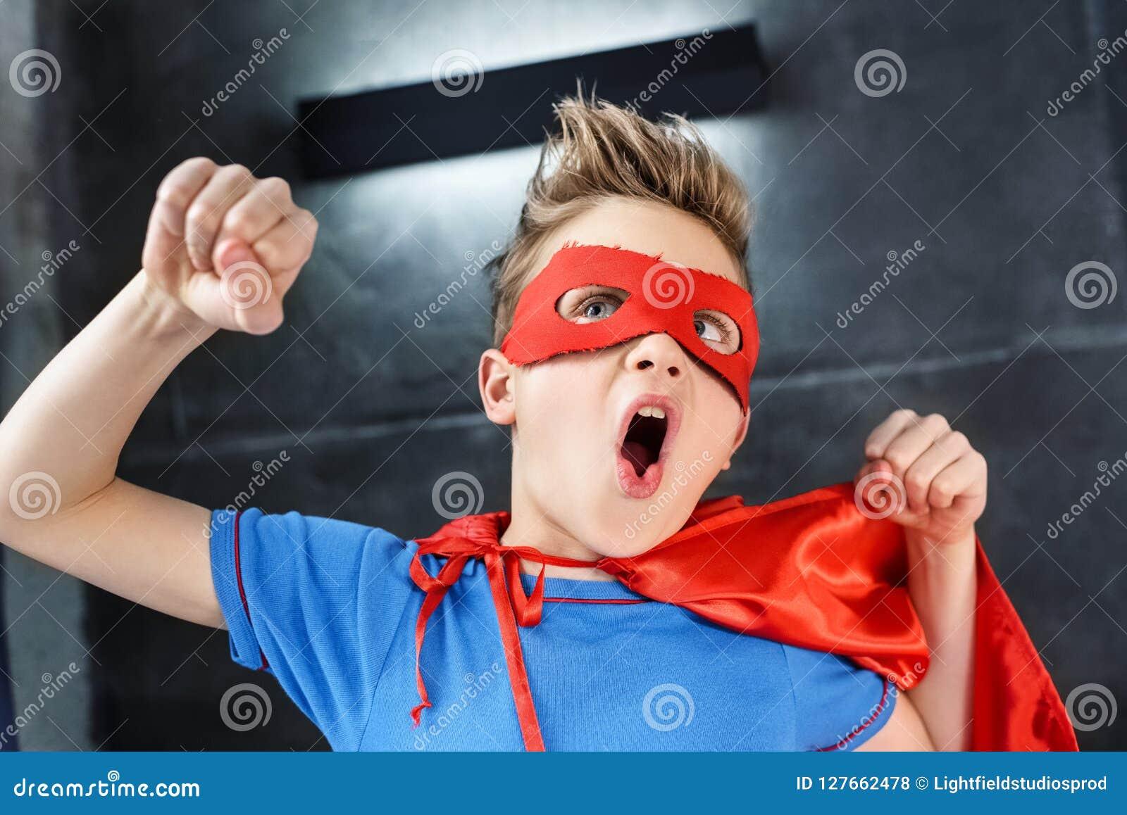 Weinig jongen in het rode superherokostuum gesturing