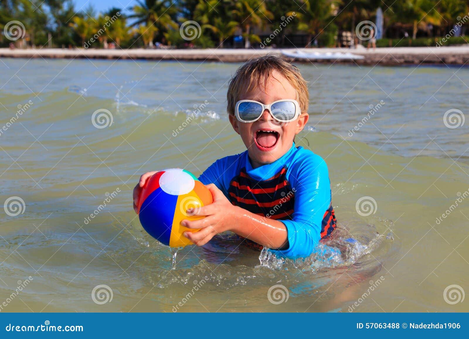 Weinig jongen het spelen bal op strand