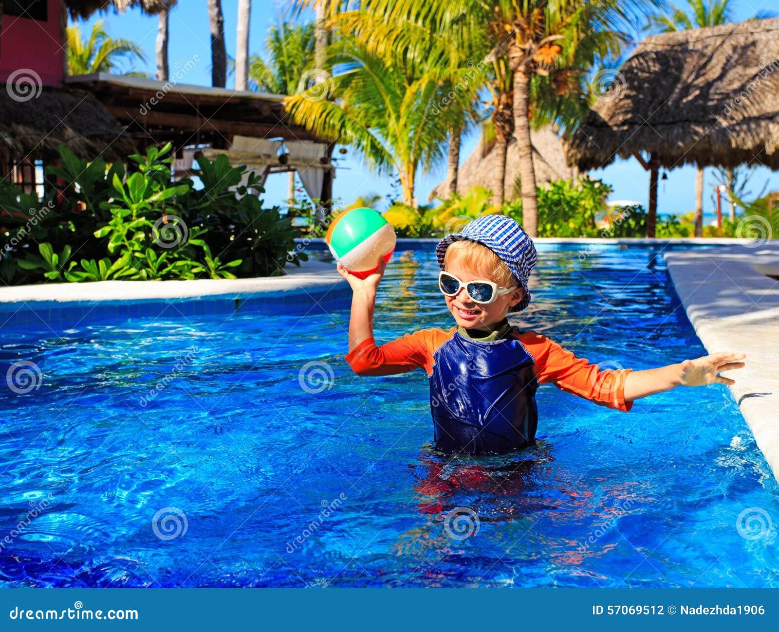 Weinig jongen het spelen bal in zwembad op strand