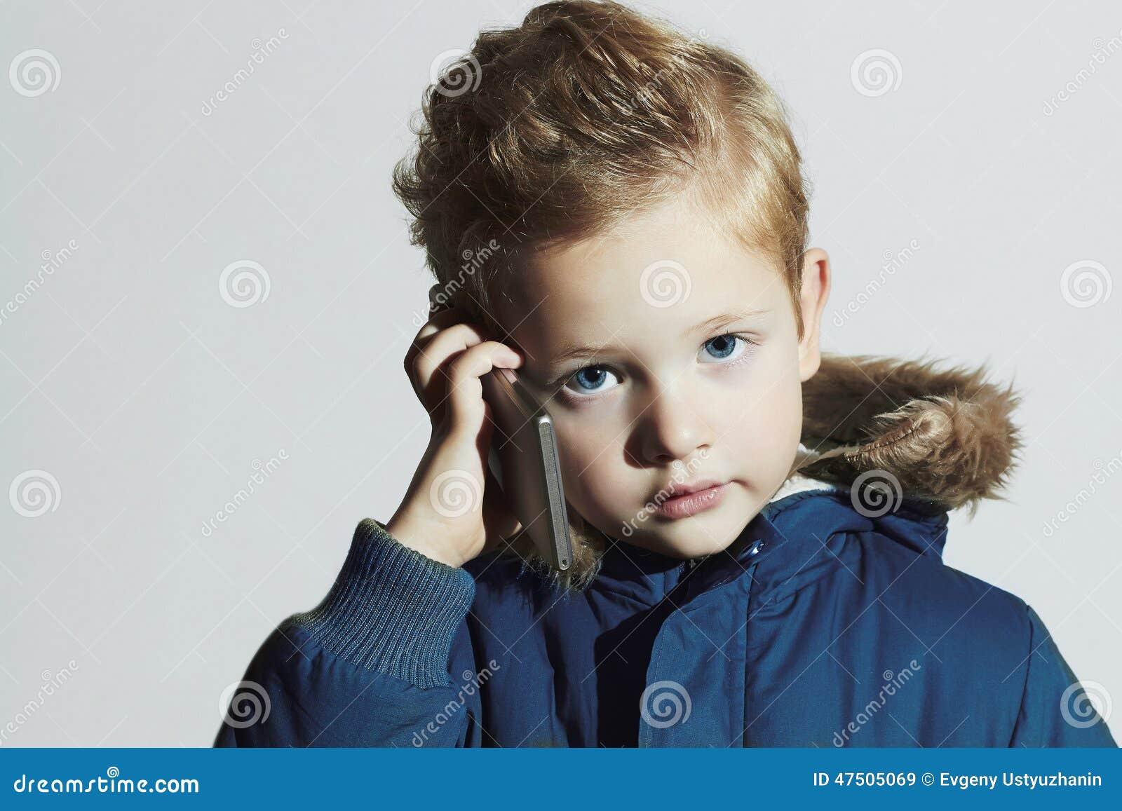 Weinig jongen met cellphone modern kind in de winterlaag de jonge geitjes van de manier kinderen - Teen moderne ruimte van de jongen ...