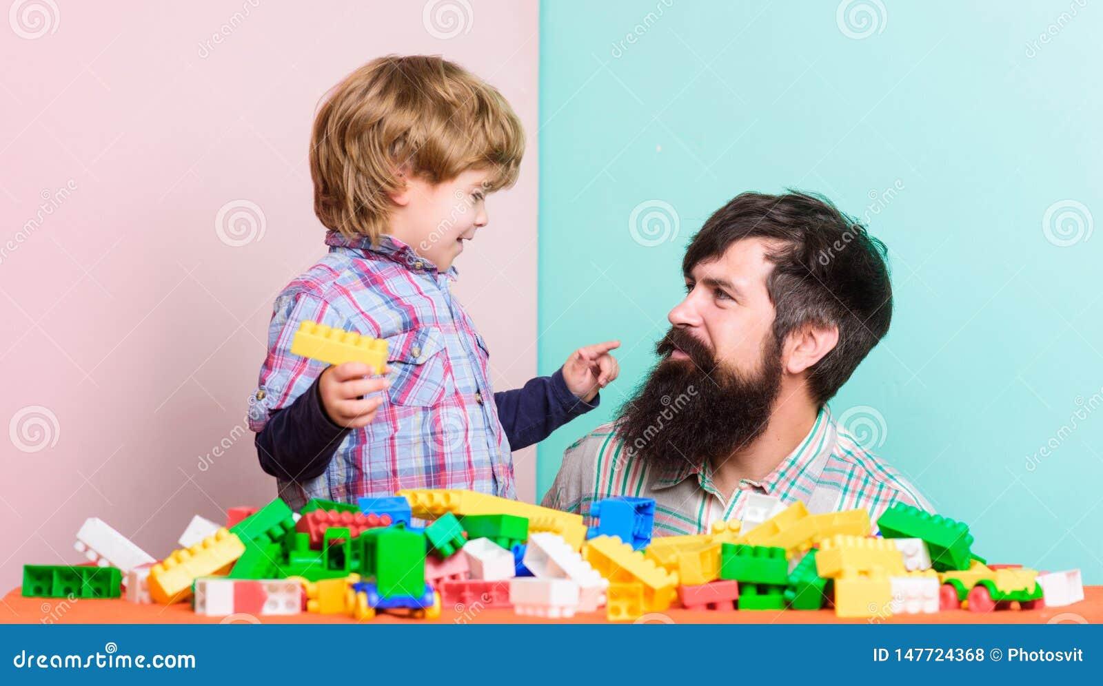 Weinig jongen met gebaarde mensenpapa die samen spelen Gelukkige Familie De zomer dreems de bouwhuis met kleurrijke aannemer