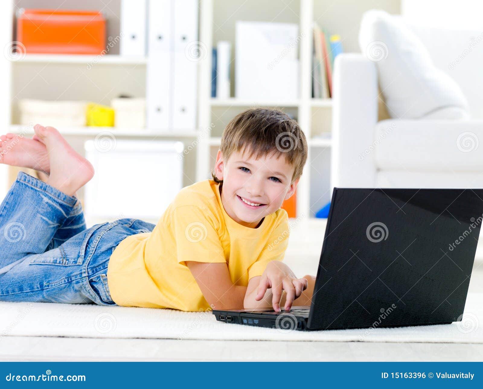 Weinig jongen met laptop