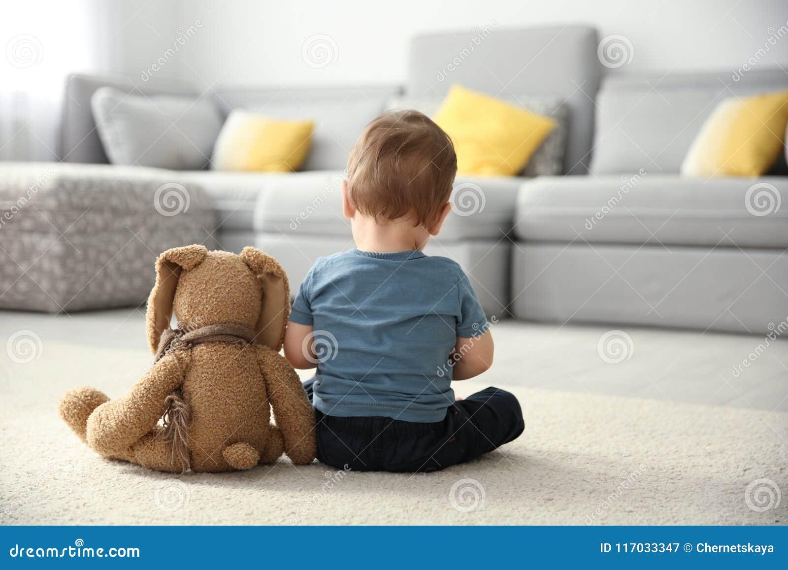 Weinig jongen met stuk speelgoed zitting op vloer in woonkamer