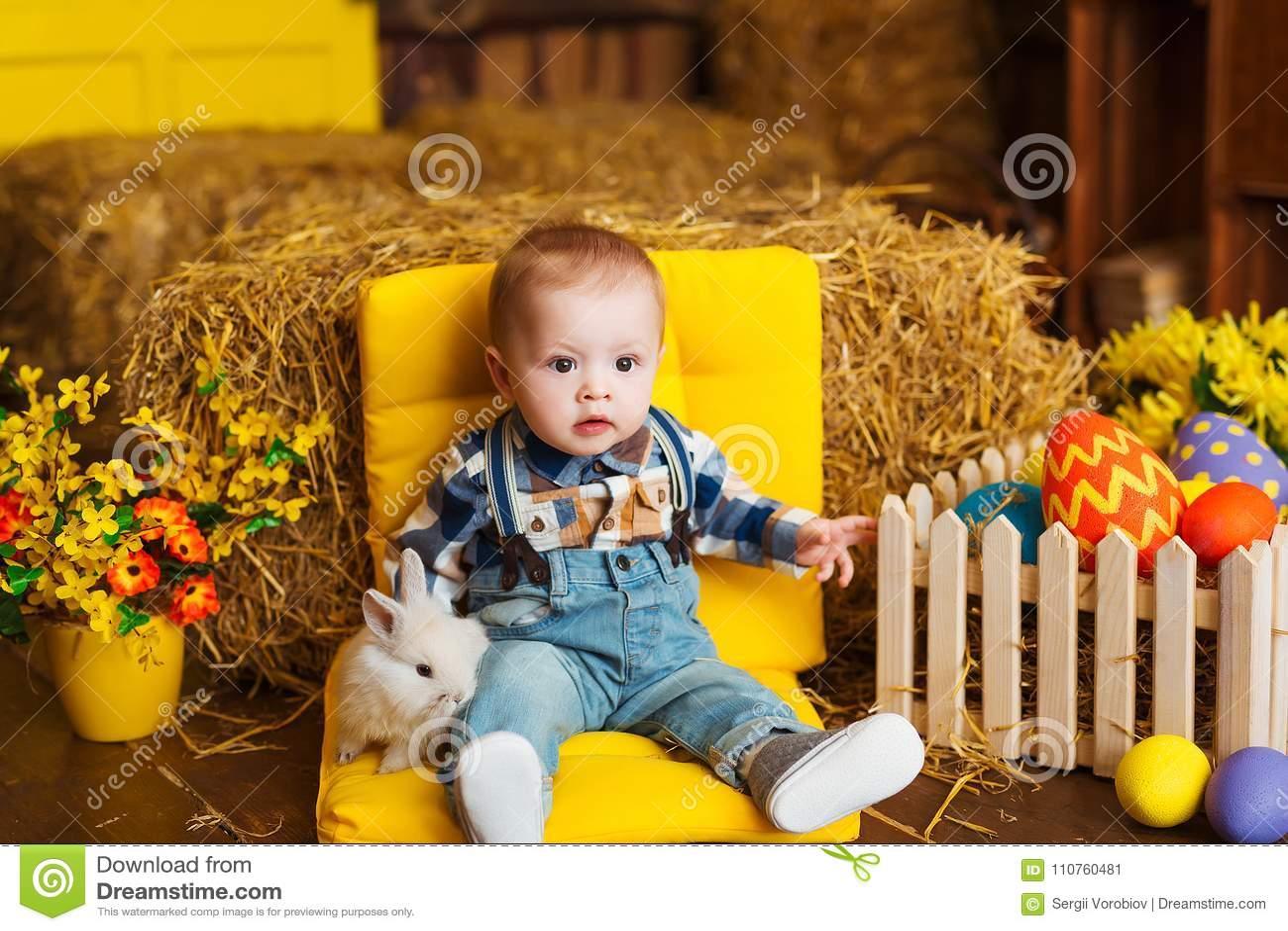 Weinig jongen met wit konijn spelen en wortel die binnen De pret van de lentepasen voor kinderen Gelukkig kinderjarenconcept