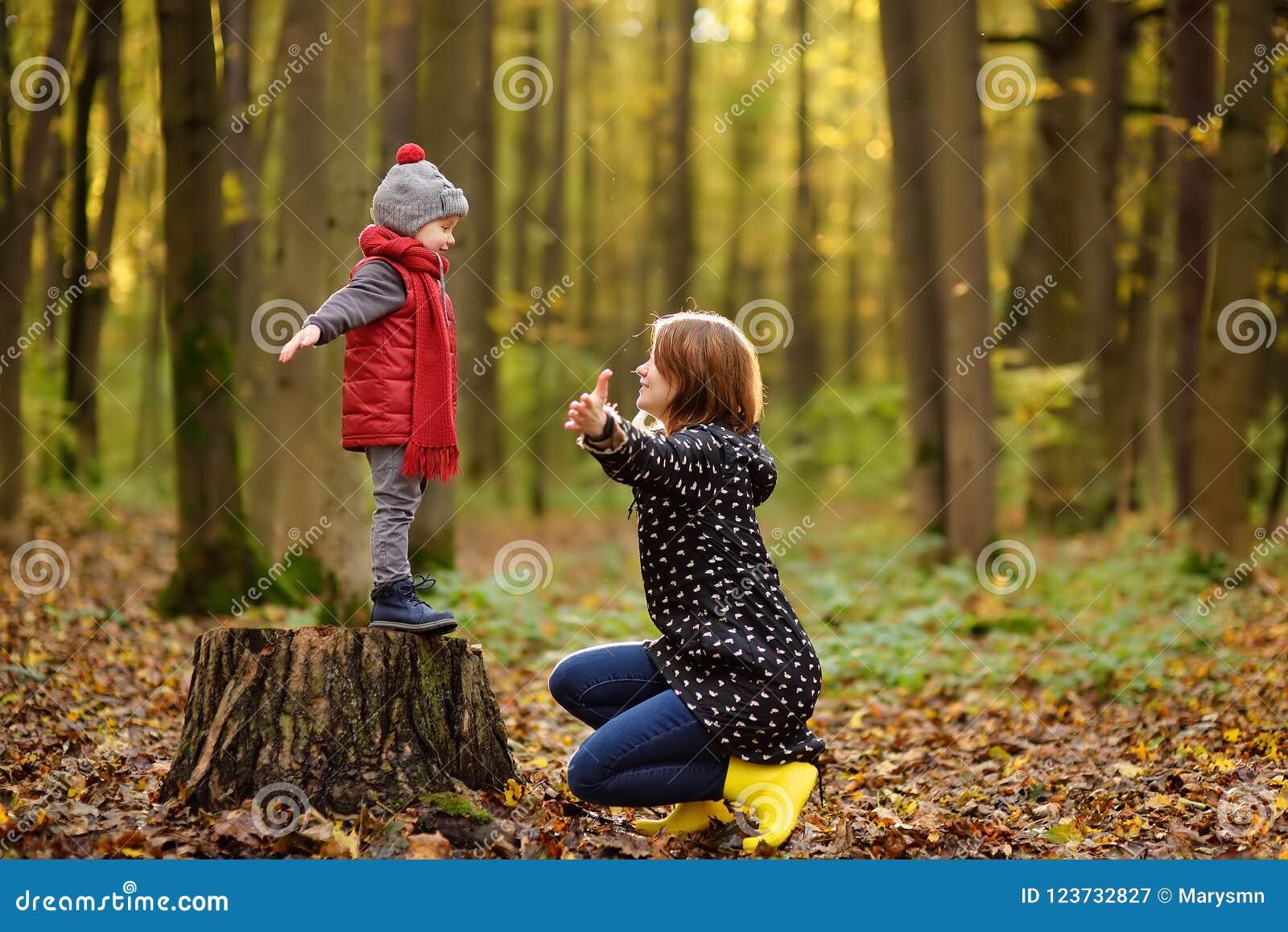 Weinig jongen met zijn jonge moeder tijdens wandeling in het bos
