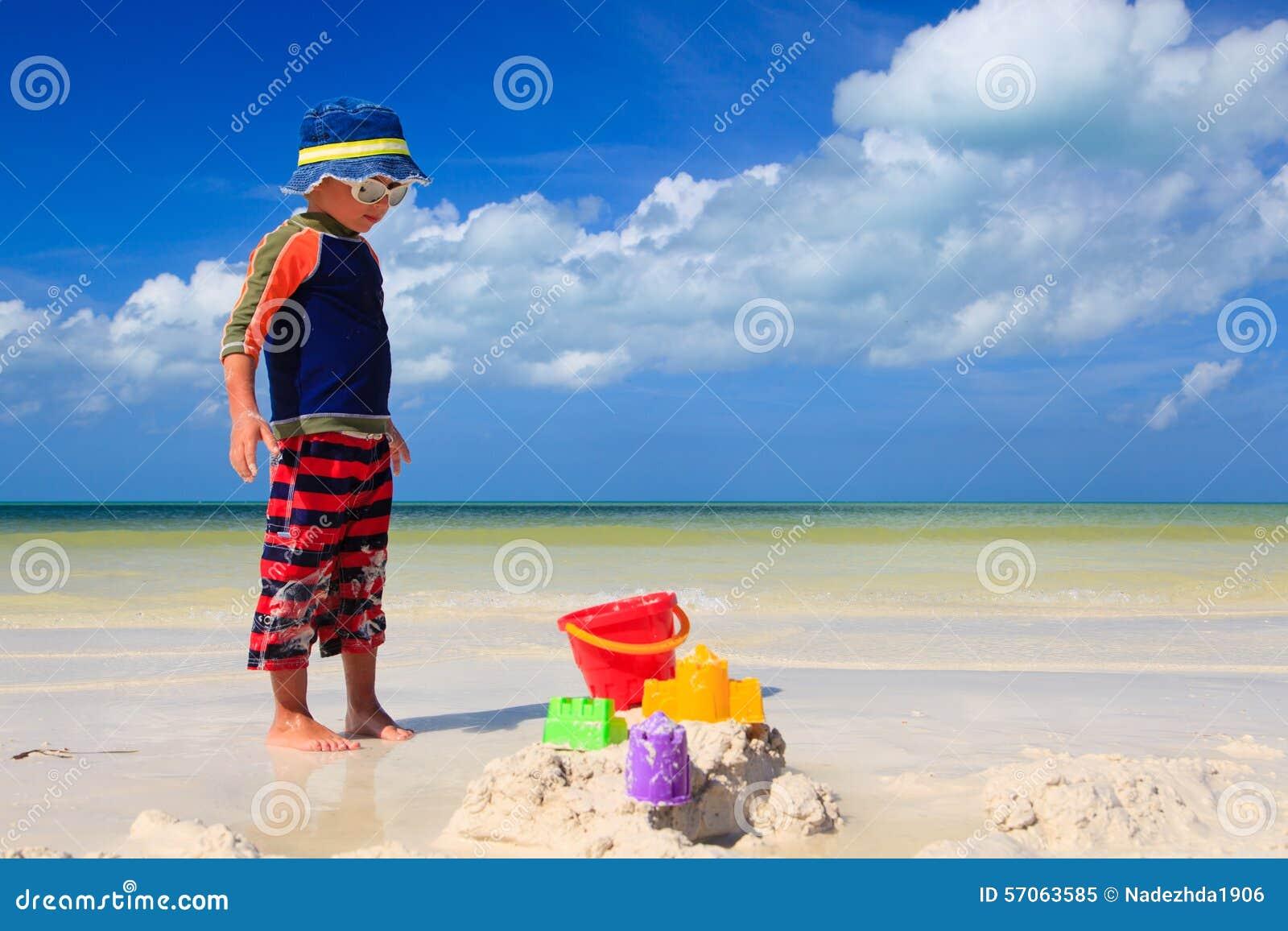 Weinig jongens gravend zand op tropisch strand