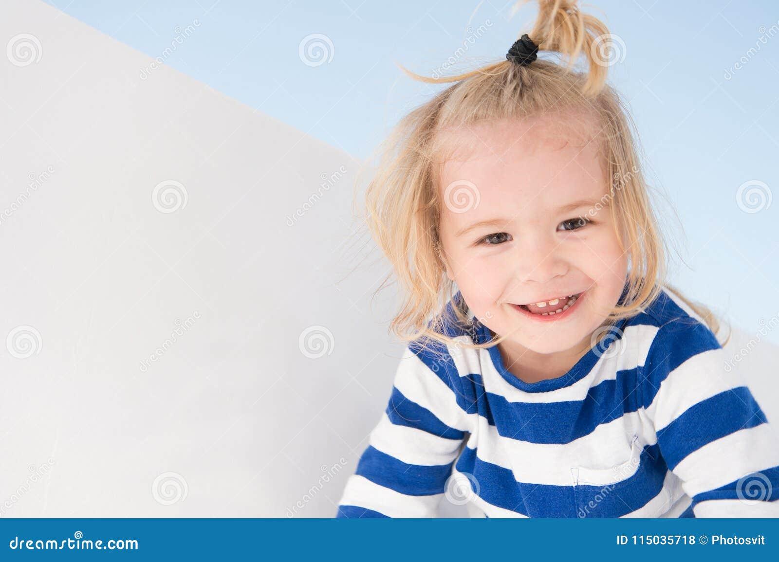 Weinig jongensglimlach in marinekleren Het gelukkige kind geniet van zonnige dag Jong geitje die met blonde haarpaardestaart glim