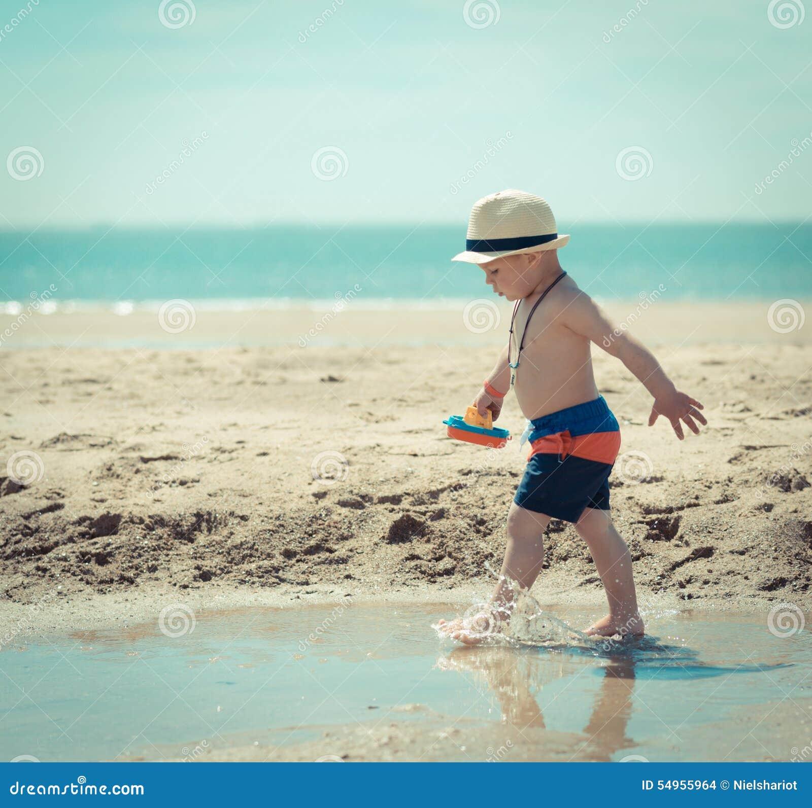 Weinig jongenskind die op het strand lopen die shell inspecteren