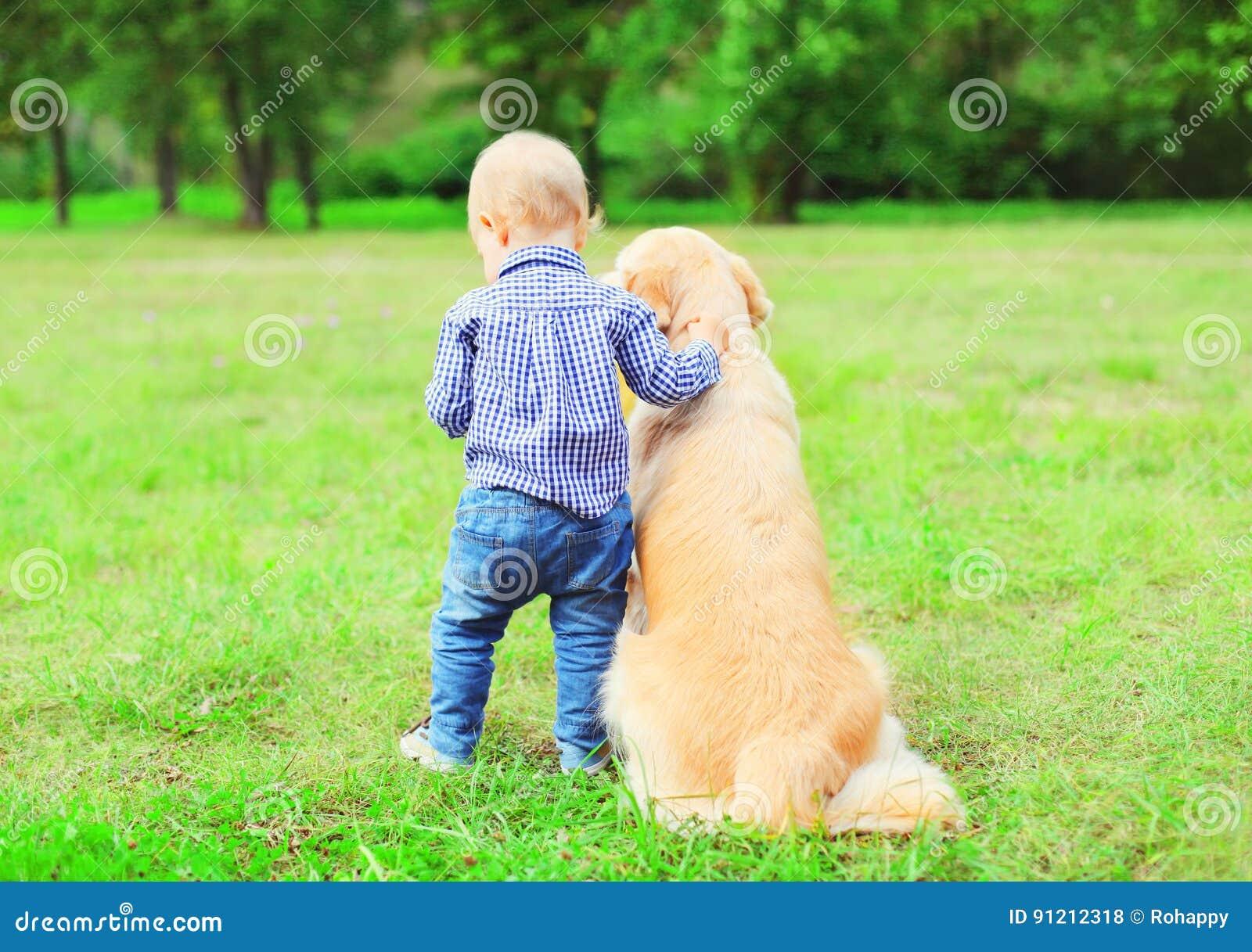 Weinig jongenskind en Golden retrieverhond samen in openlucht, de zomerpark