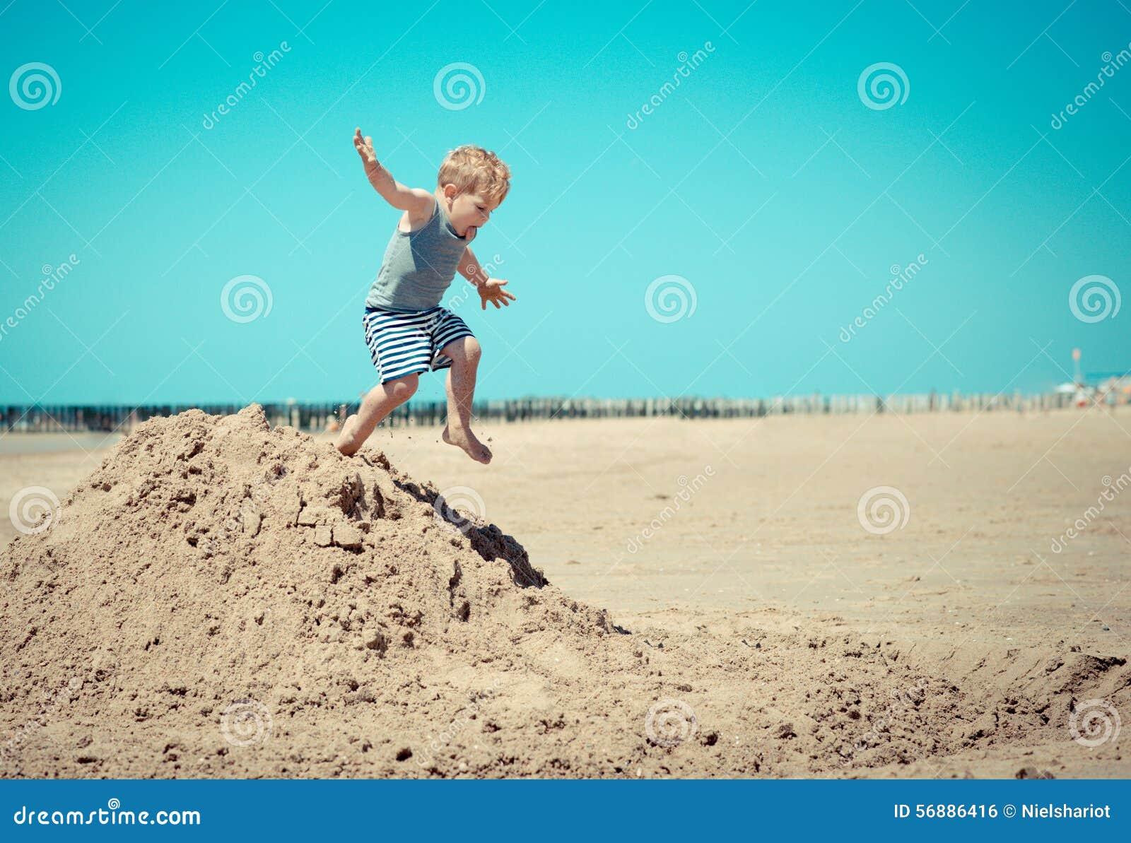 Weinig jongenskind springt van een berg op het strand