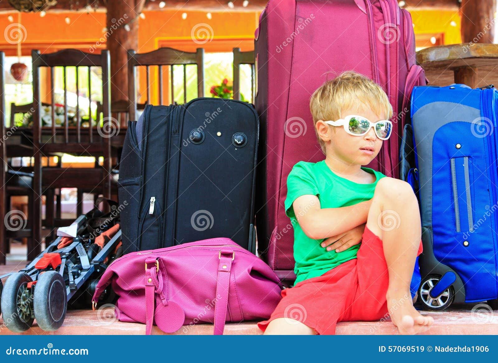 Weinig jongenszitting op koffers klaar te reizen
