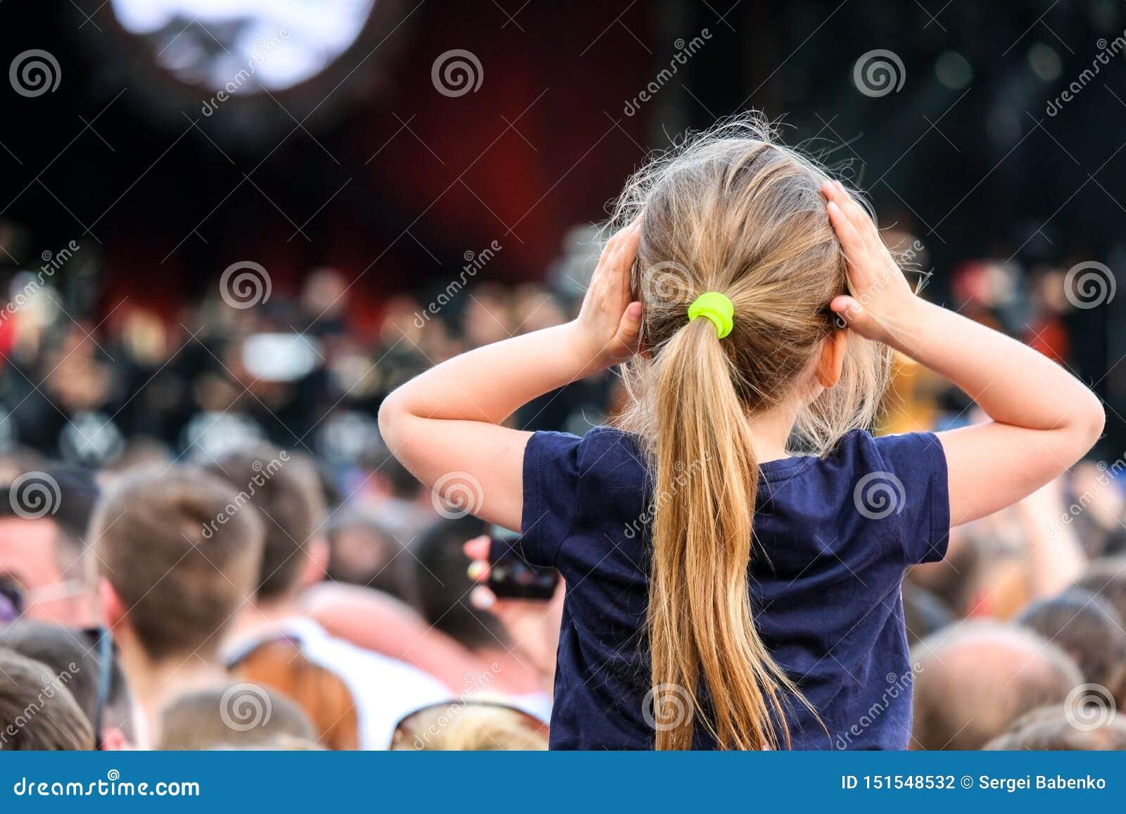 Weinig Kaukasisch meisje die op de schouders van de vader op het overleg in de menigte letten
