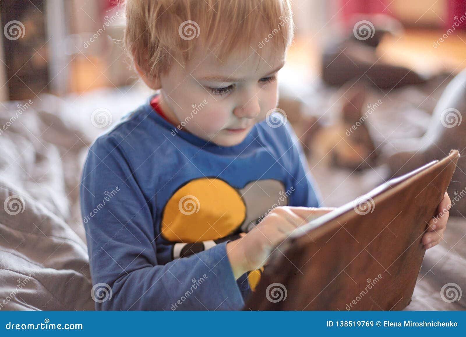 Weinig Kaukasische babyjongen zit op de bank gebruikend een tablet, wat betreft het scherm Rood haar, vrijetijdskleding, binnen,