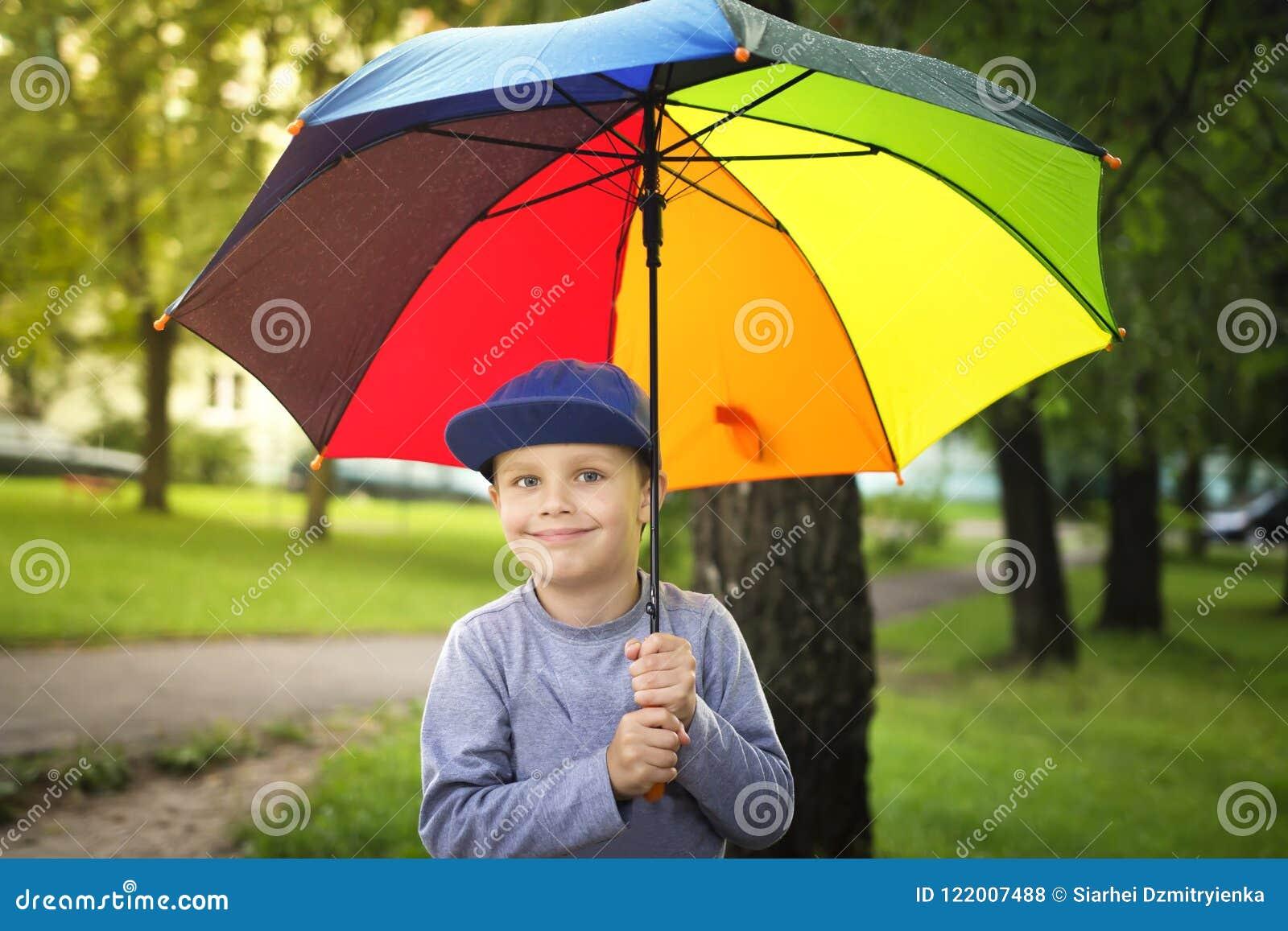 Weinig Kaukasische jongen met kleurrijke paraplu in park na regen op zonnige de zomerdag