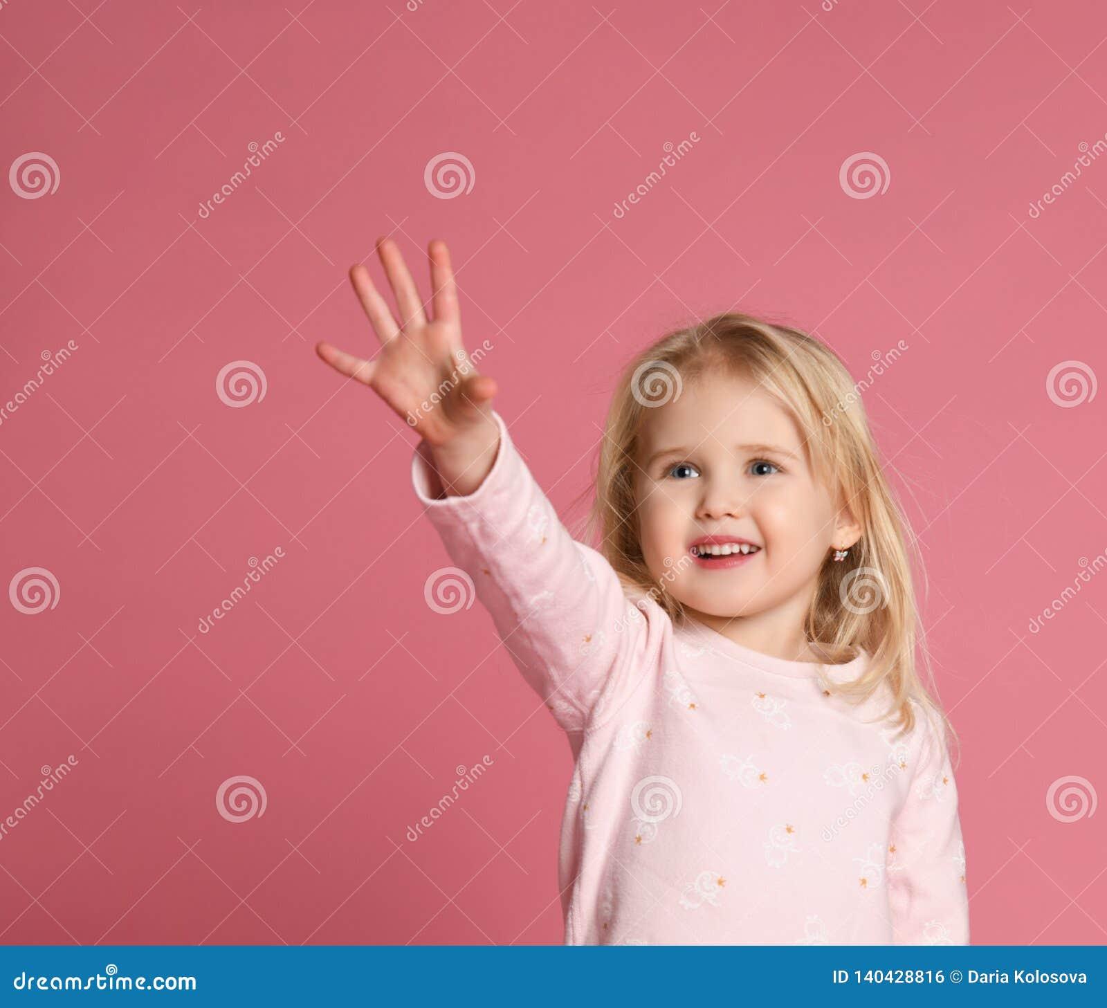 Weinig leuk blonde van het meisjeskind in een roze kostuum is schuw op een roze achtergrond