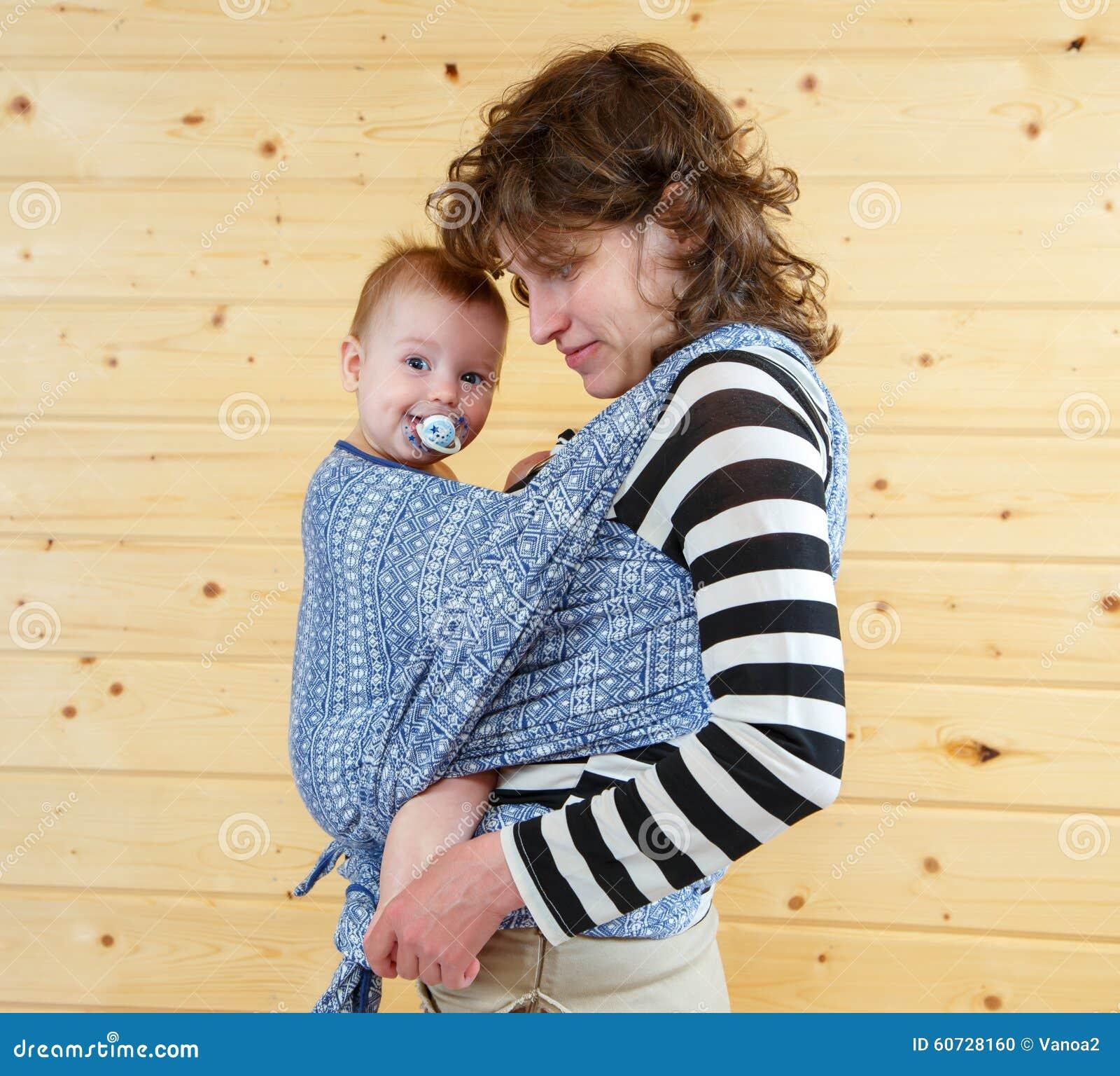 Weinig leuke baby met soother in het dragen van slinger