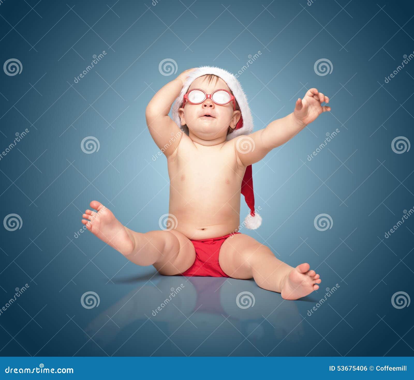 Weinig leuke baby in rode Kerstmanhoed en rode glazen