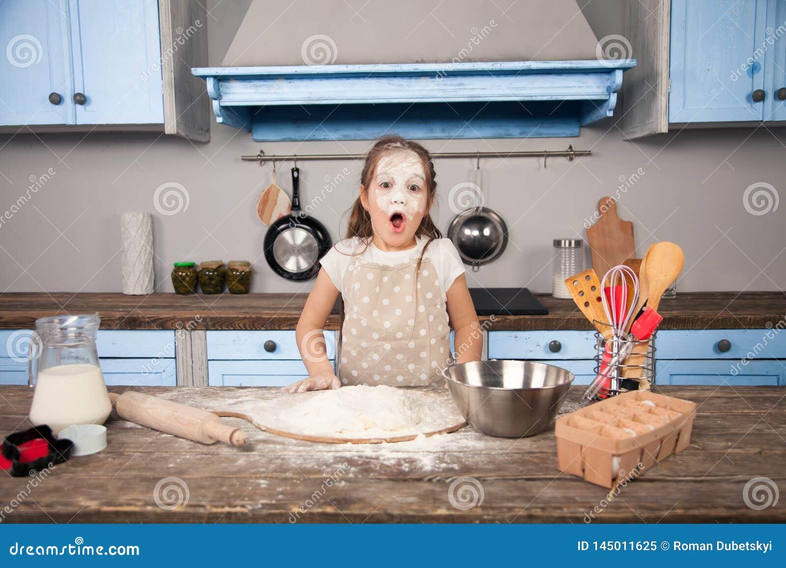 Weinig meisje van de kinddochter helpt haar moeder in de keuken om bakkerij, koekjes te maken Zij heeft overal een vloed haar