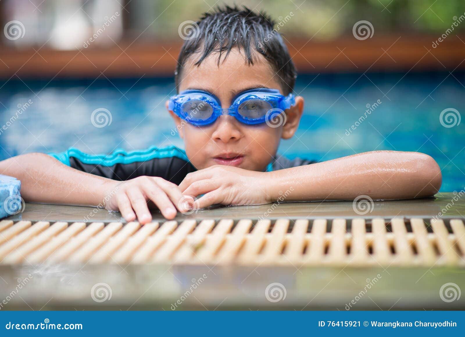 Weinig mengelings Aziatische Arabische jongen die bij zwembad openluchtactiviteit zwemmen