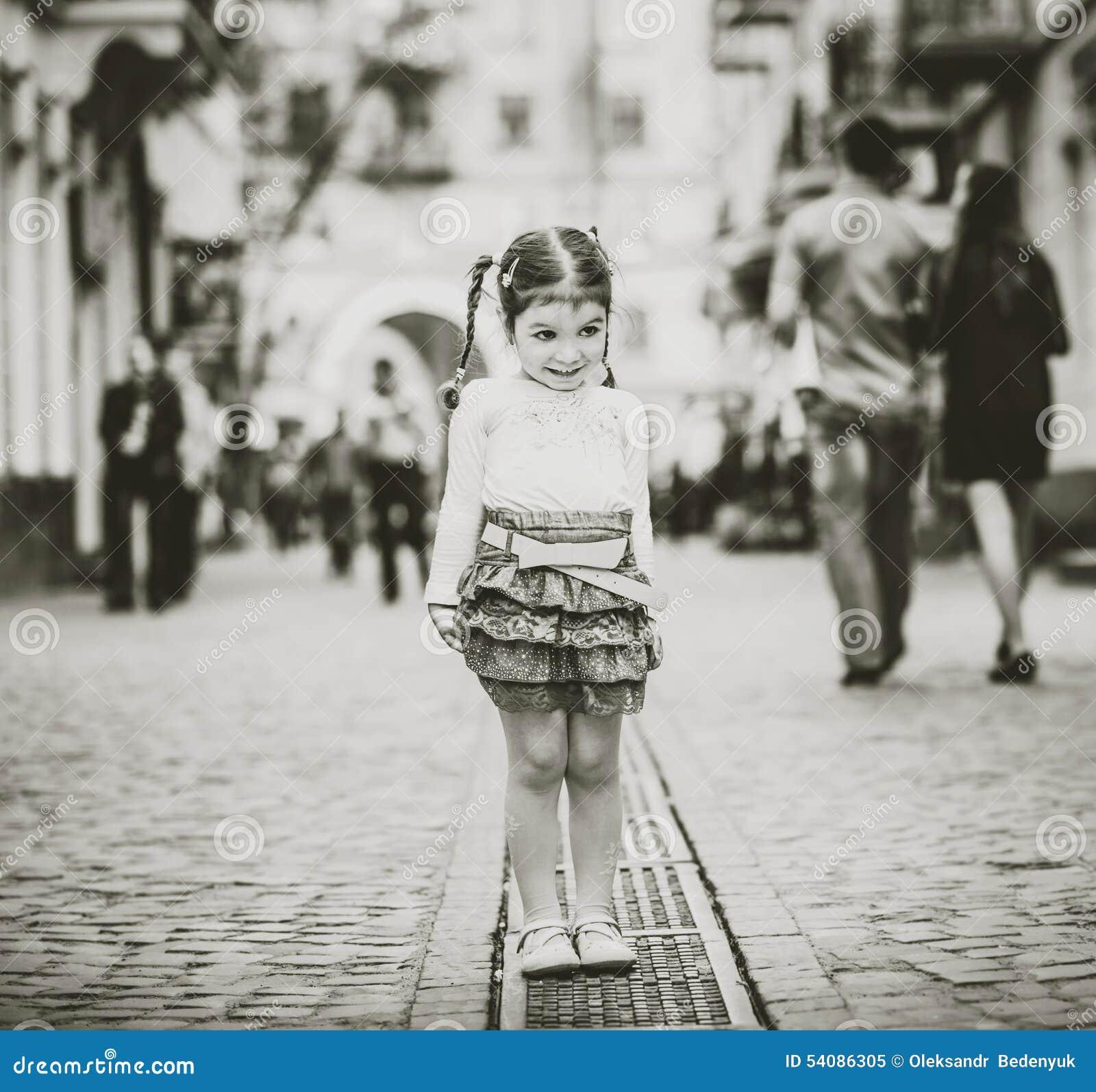 Weinig mooi meisje die op de stadsstraat lopen