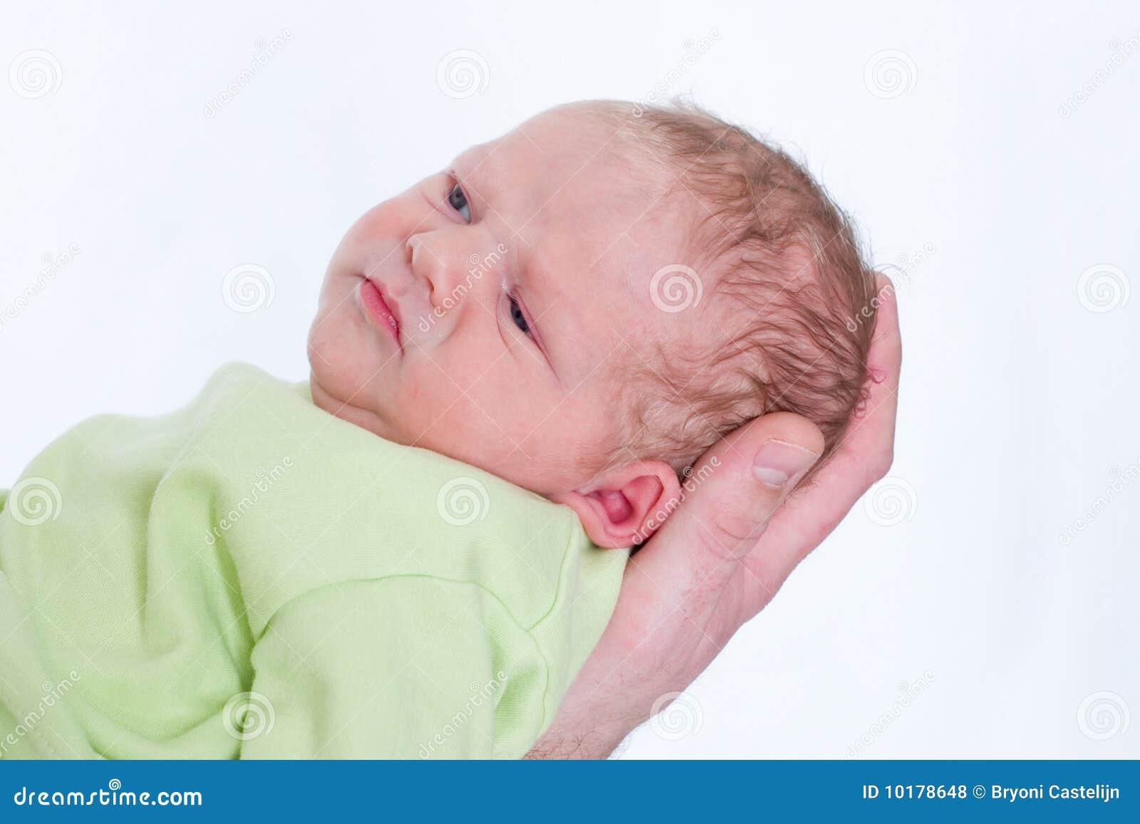 Weinig pasgeboren baby op zijn vaders overhandigt het fronsen
