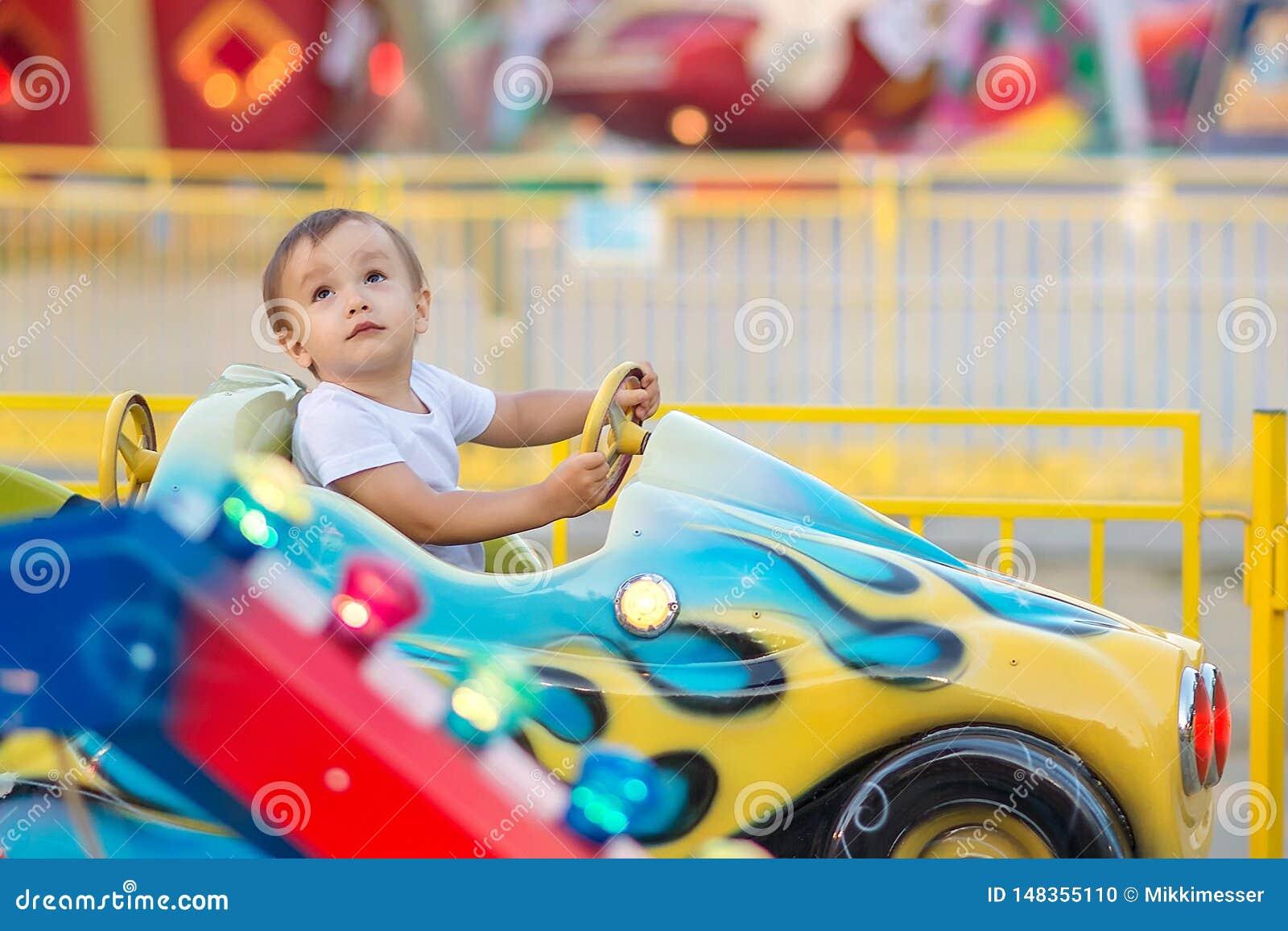Weinig peuter in themapark: een jongen in wit overhemd die weinig auto berijden op vrolijk gaat rond, helder vermaak op achtergro