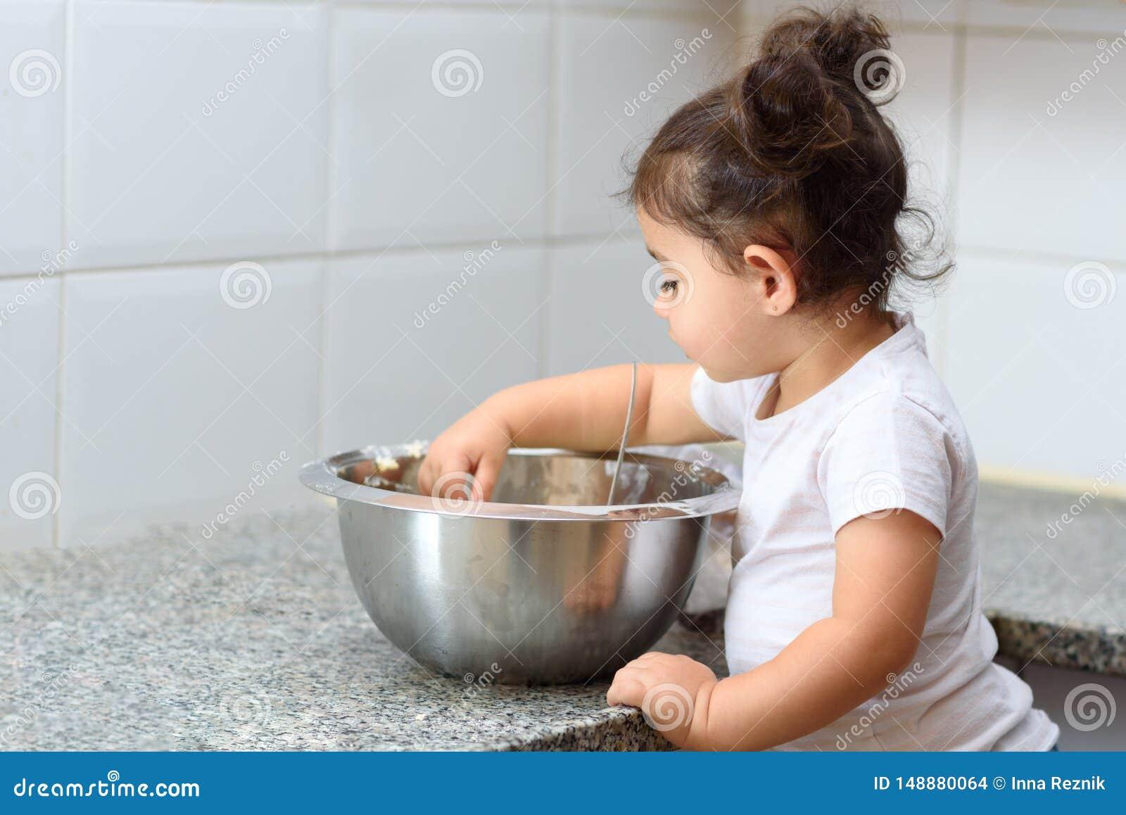 Weinig peutermeisje het kneden deeg in keuken