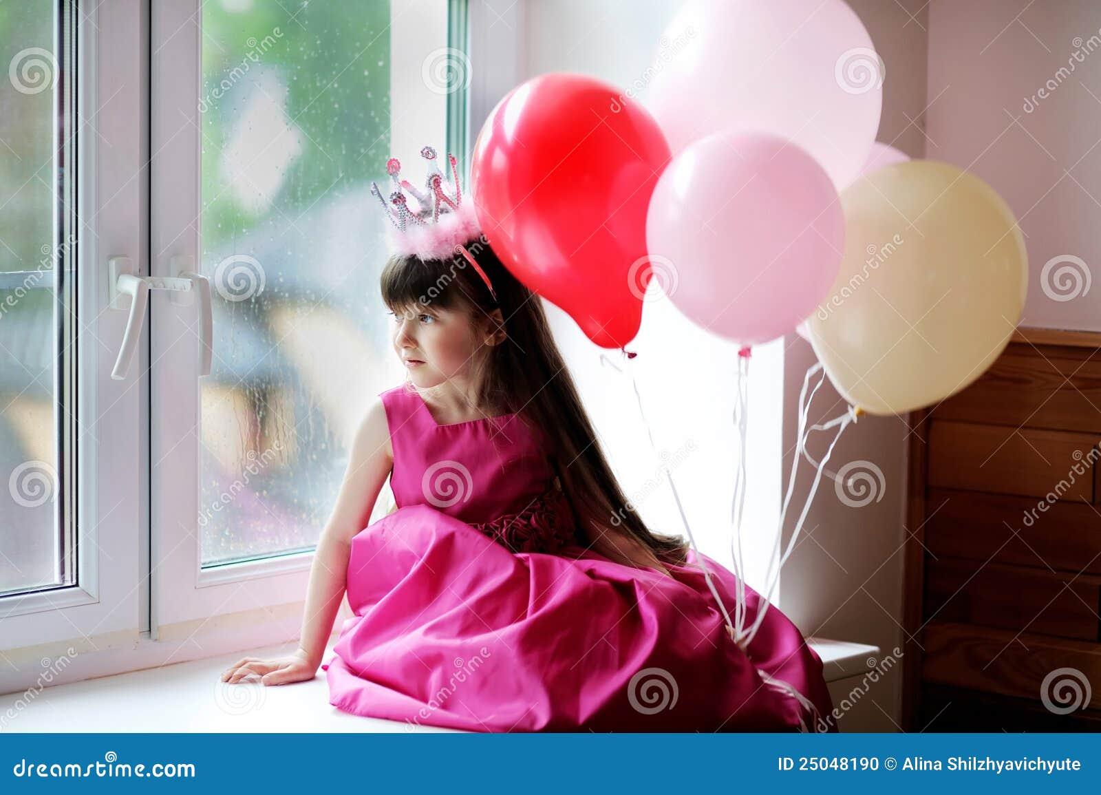 Weinig prinses in roze kledingsholding baloons