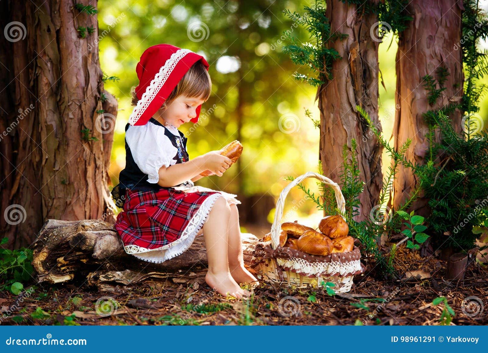Weinig Rode Berijdende Kap in het bos zit op een logboek met een mand van pastei