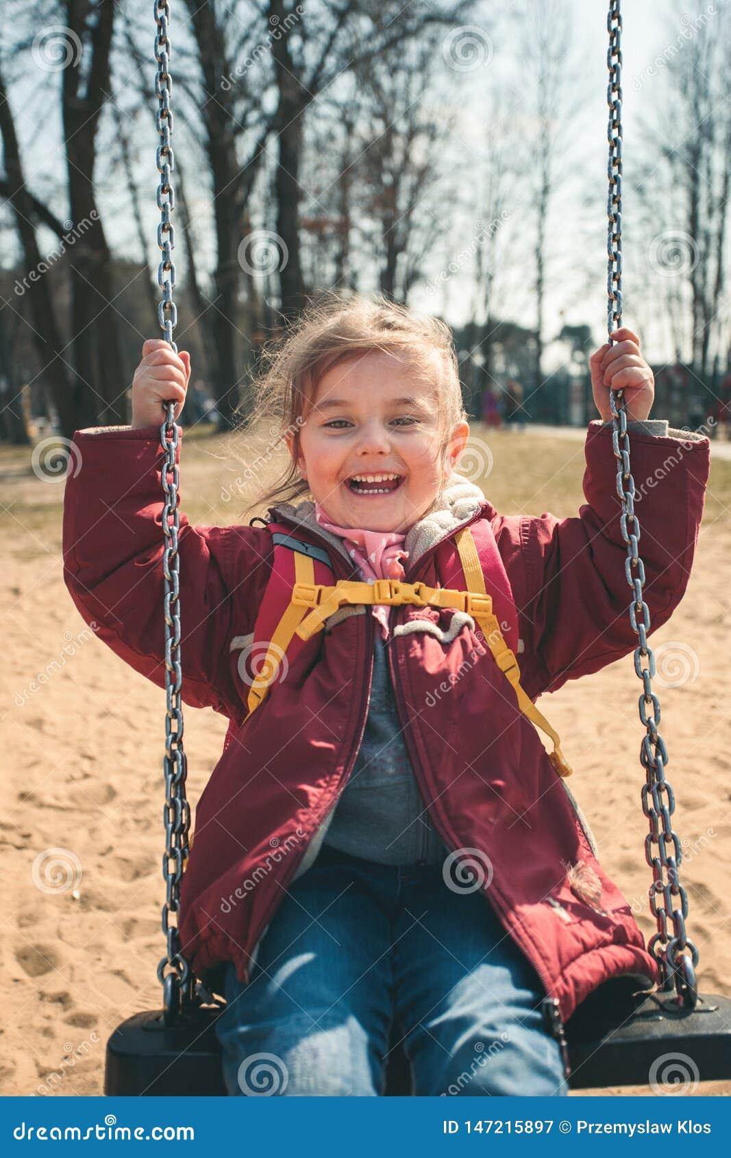 Weinig smilling gelukkig meisje die in een park op zonnige de lentedag slingeren