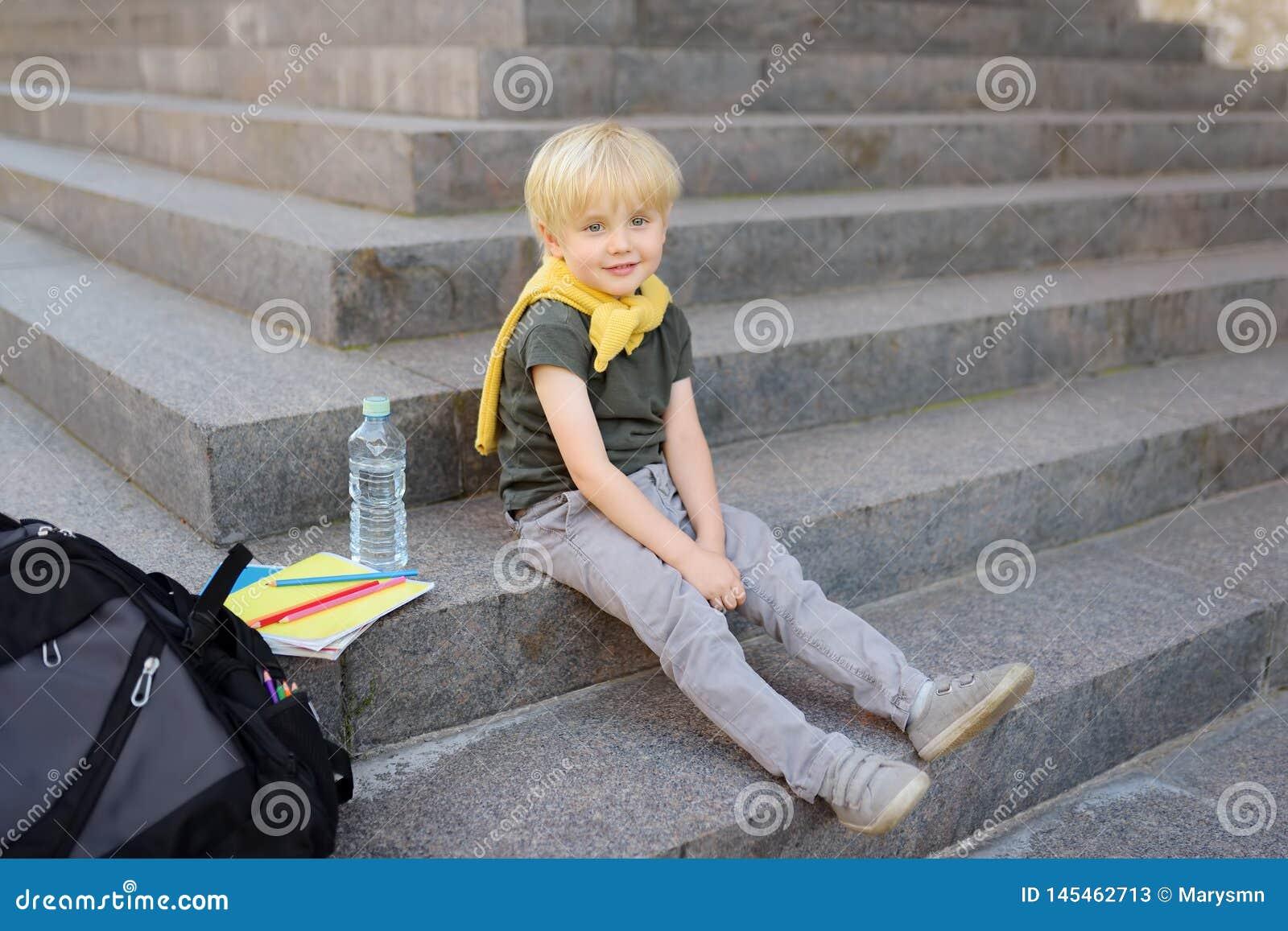 Weinig studentenzitting op trap dichtbij het schoolgebouw Terug naar School