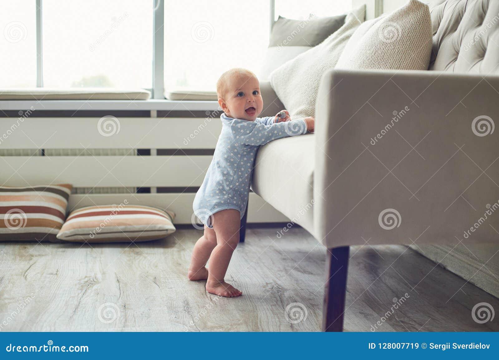 Weinig 8 van de babymaanden jongen bevindt zich thuis met steun dichtbij bank in witte ruimte