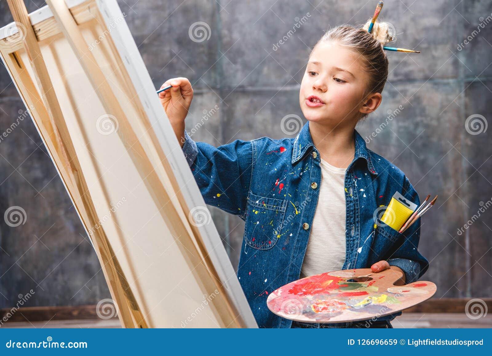 Weinig vrouwelijk kunstenaarsholding palet en het schilderen beeld