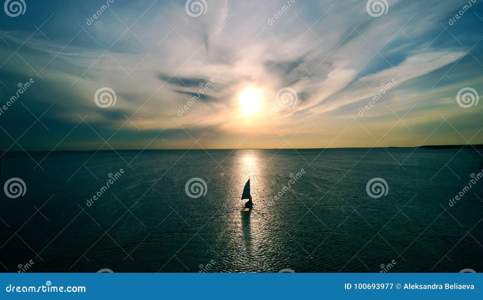 Weinig witte boot die op het water naar de horizon in de stralen van de het plaatsen zon drijven Mooie wolken met geel hoogtepunt