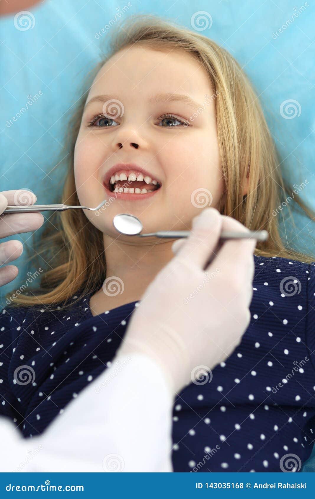 Weinig zitting van het babymeisje bij tandstoel met open mond tijdens mondelinge controle omhoog terwijl arts Bezoekend tandartsb