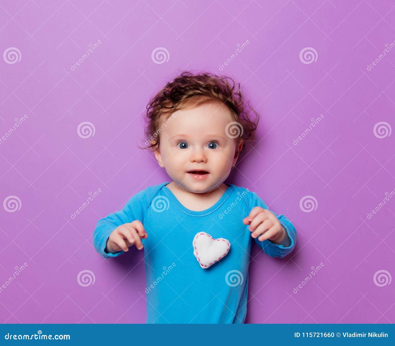 Weinig zuigelingsbaby met het stuk speelgoed van de hartvorm