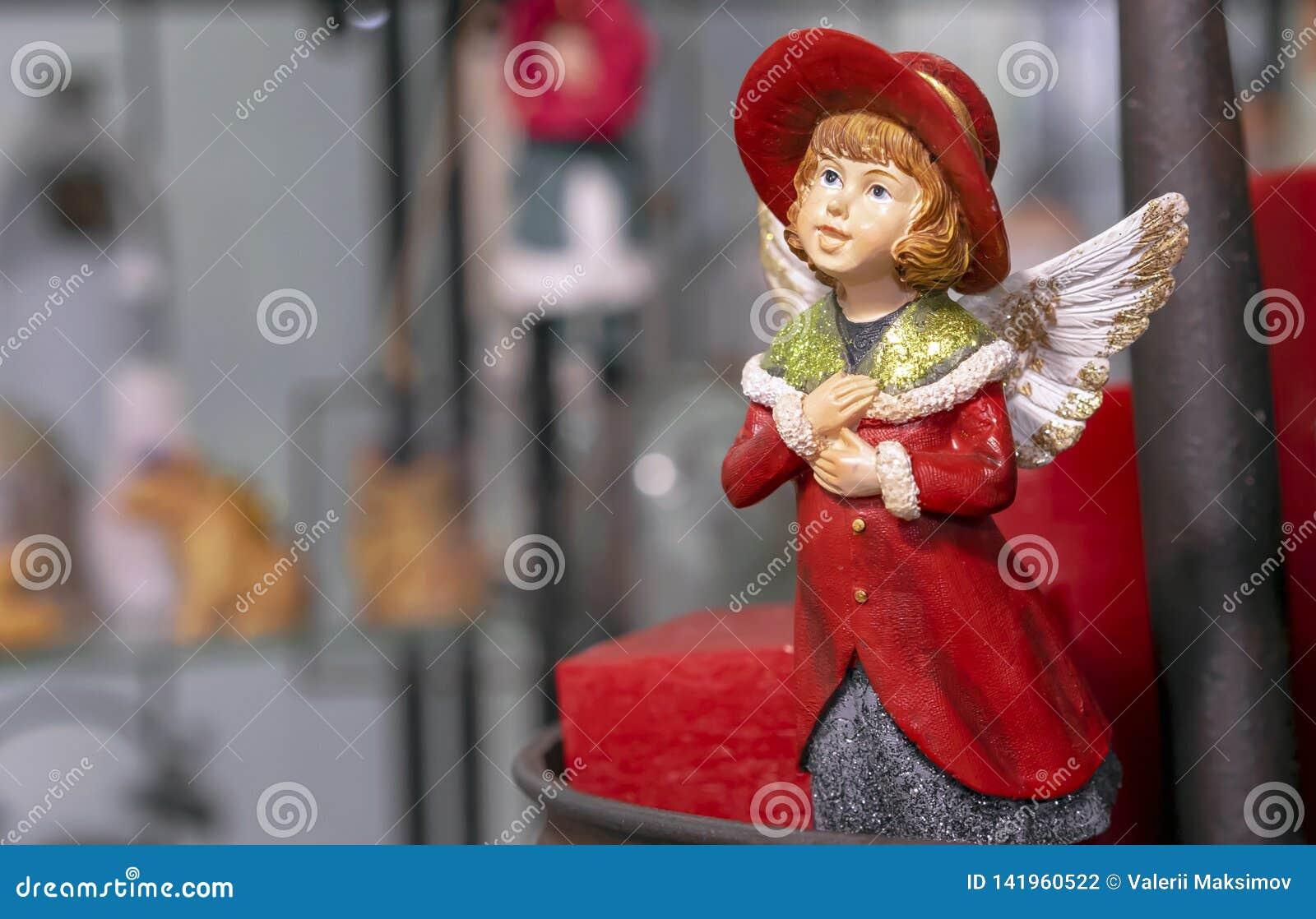 Weinlesefigürchen eines Mädchens in einem roten Mantel mit Engelsflügeln