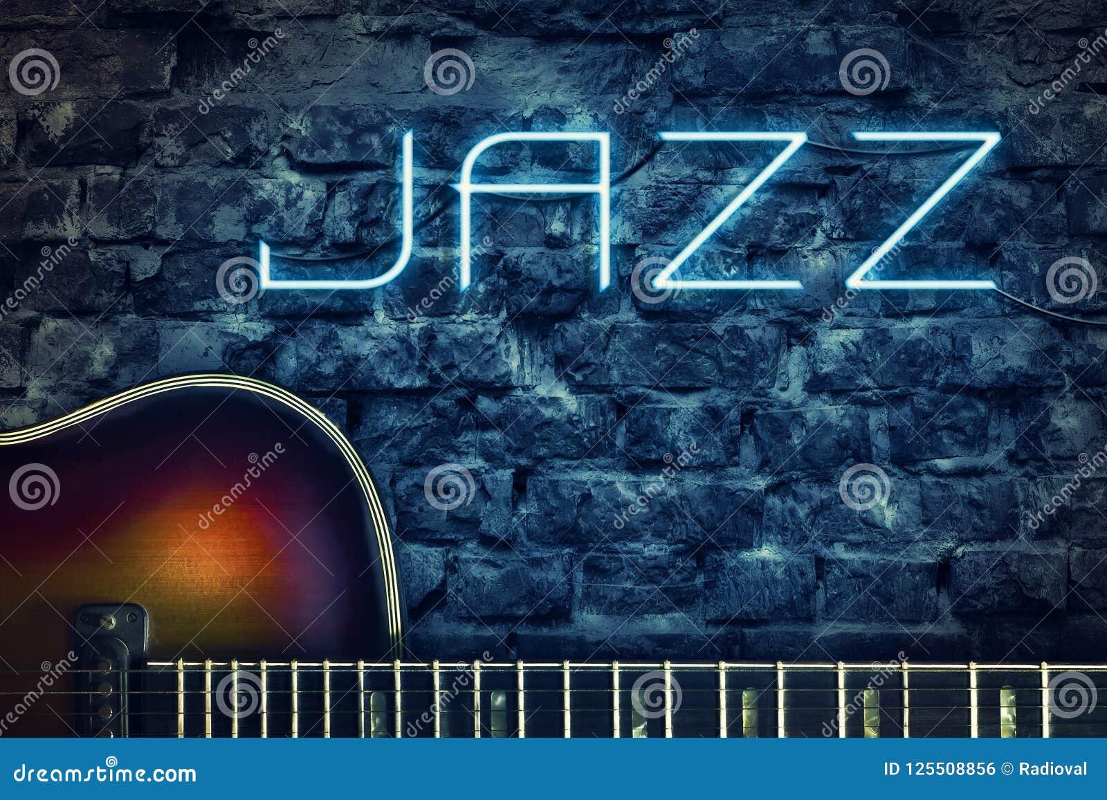 Weinlesegitarre und ein Neonaufschrift Jazz auf dem Hintergrund einer alten Backsteinmauer Konzeptmusik