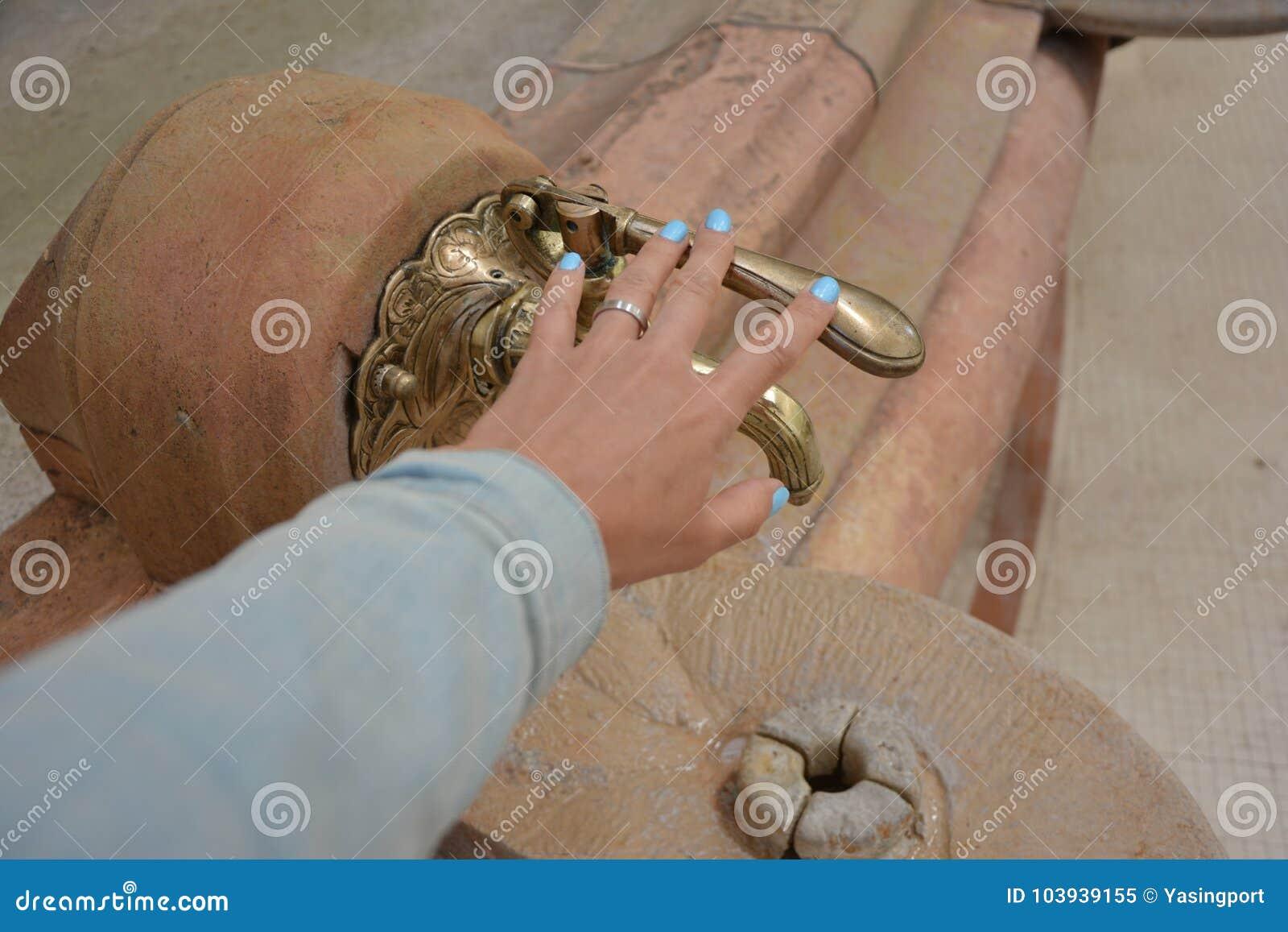 Weinlesehahn mit einer Quelle des Mineralwassers und der Hand der Frauen