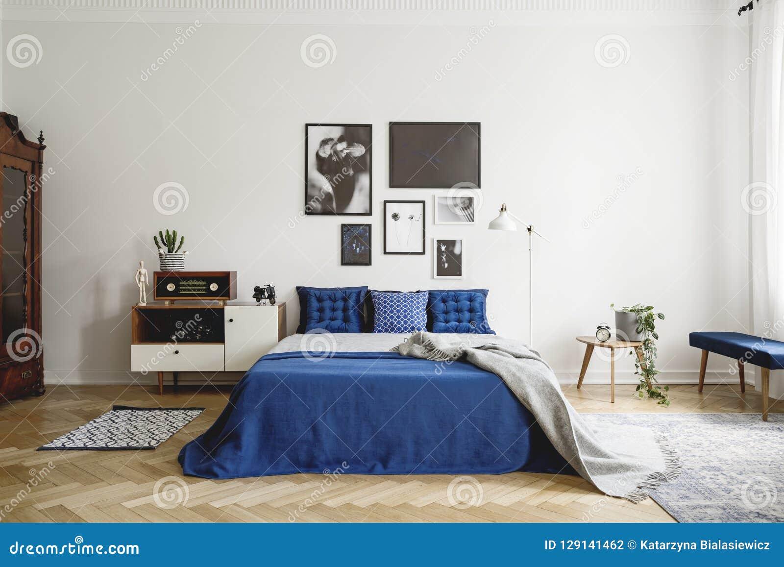 Weinleseschlafzimmerinnenraum mit Nachttisch, Königgrößenbett mit blauer Bettwäsche und Kissen Modellgalerie auf der weißen Wand