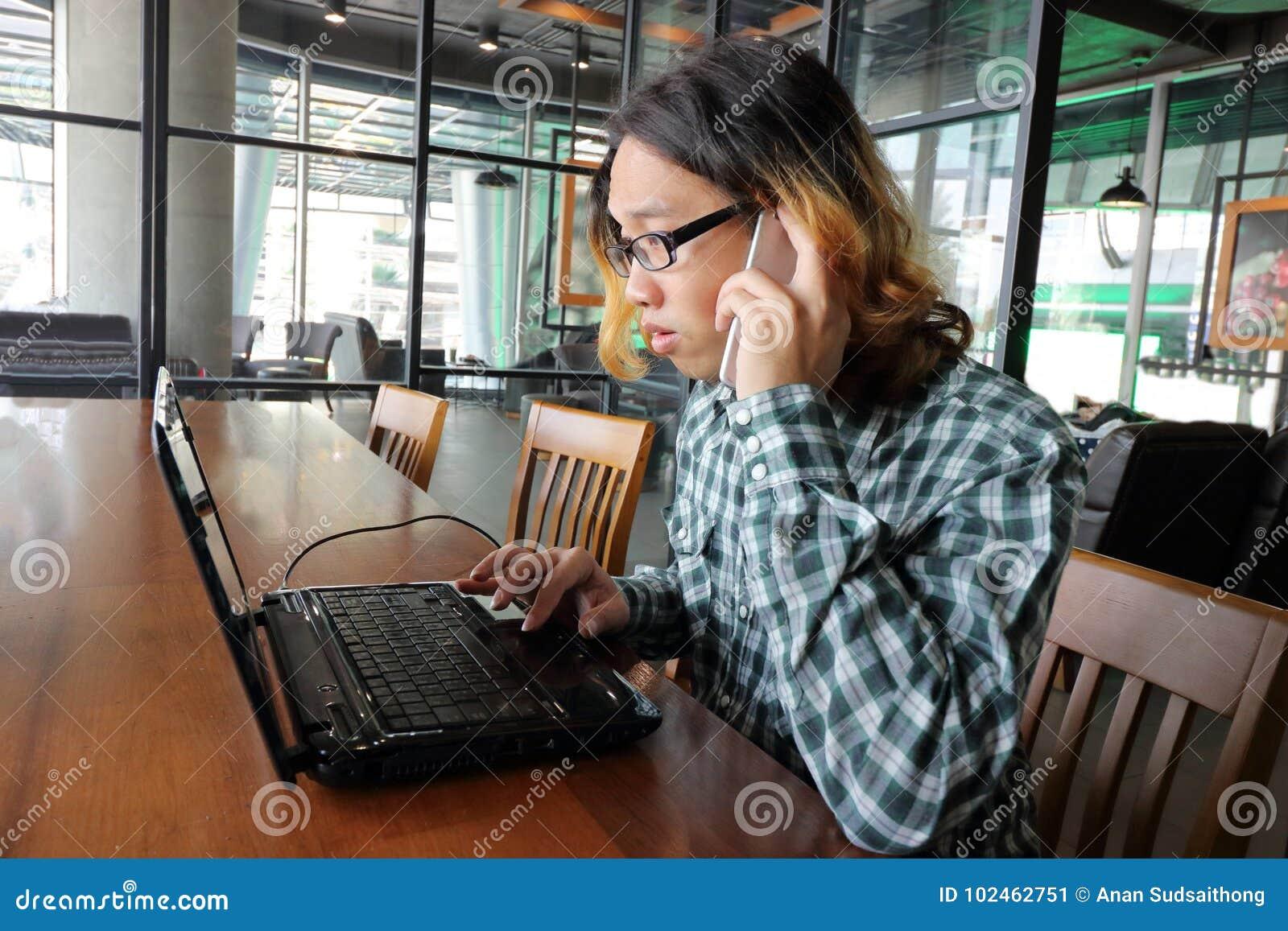 Weitwinkelschuß der jungen asiatischen Arbeitskraft, die mit Laptop und intelligentem Telefon im Büro arbeitet
