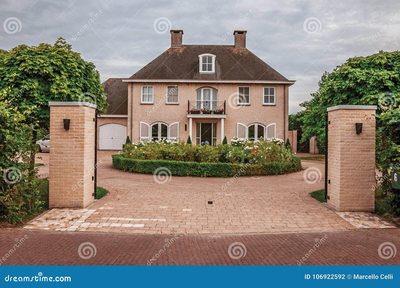 Wejściowa brama otwarta podwórze ogród w eleganckim cegła domu na chmurnym dniu przy Drimmelen